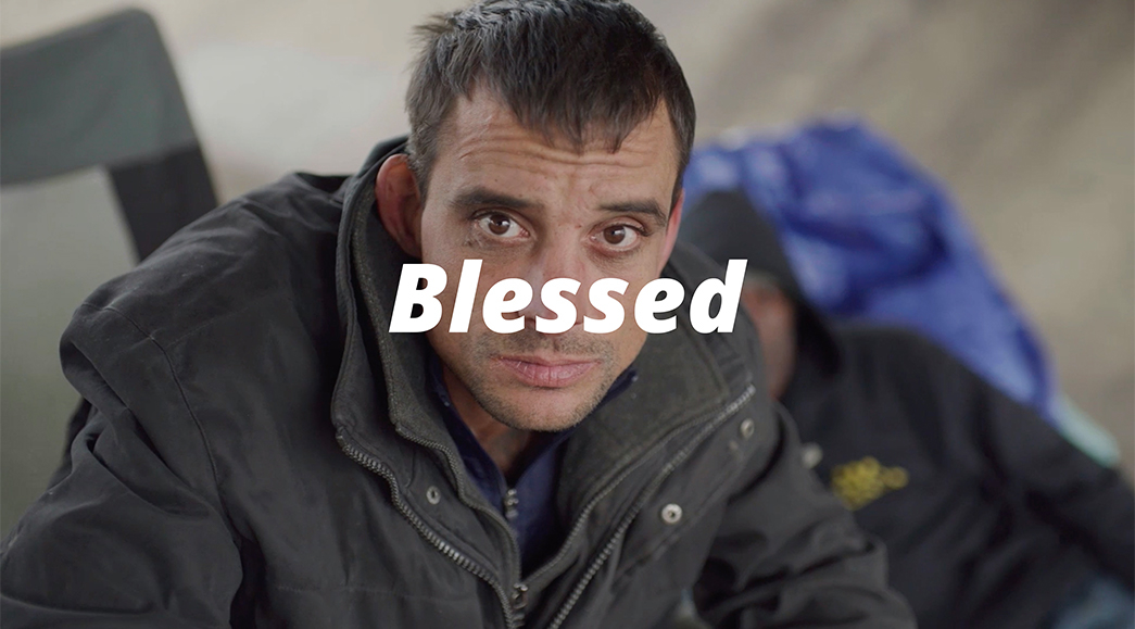 A homeless man sits on a street corner teaching the Beatitude blessed are the outcasts