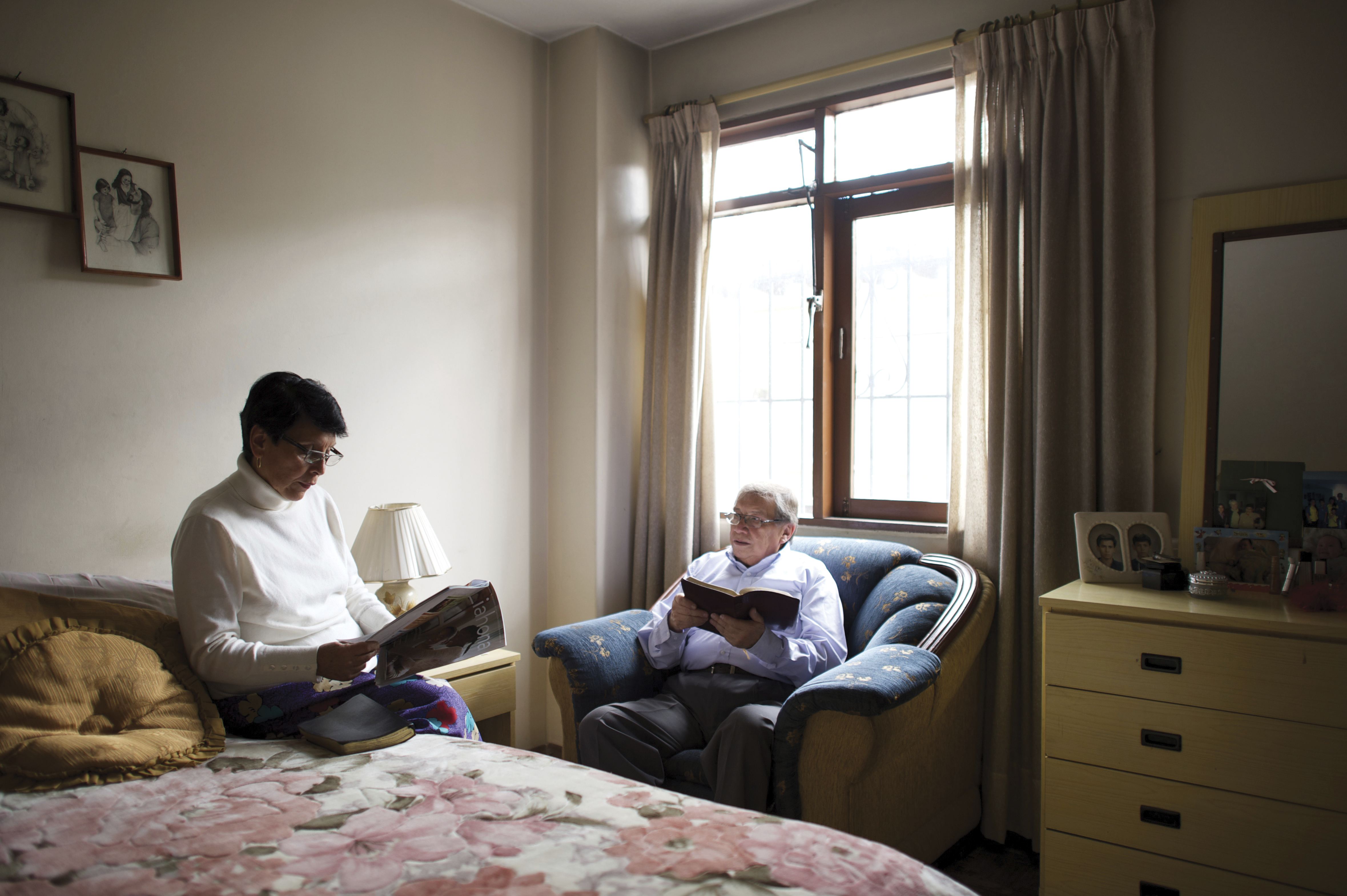 An elderly man reads the scriptures while his wife reads from a Liahona magazine in their bedroom.