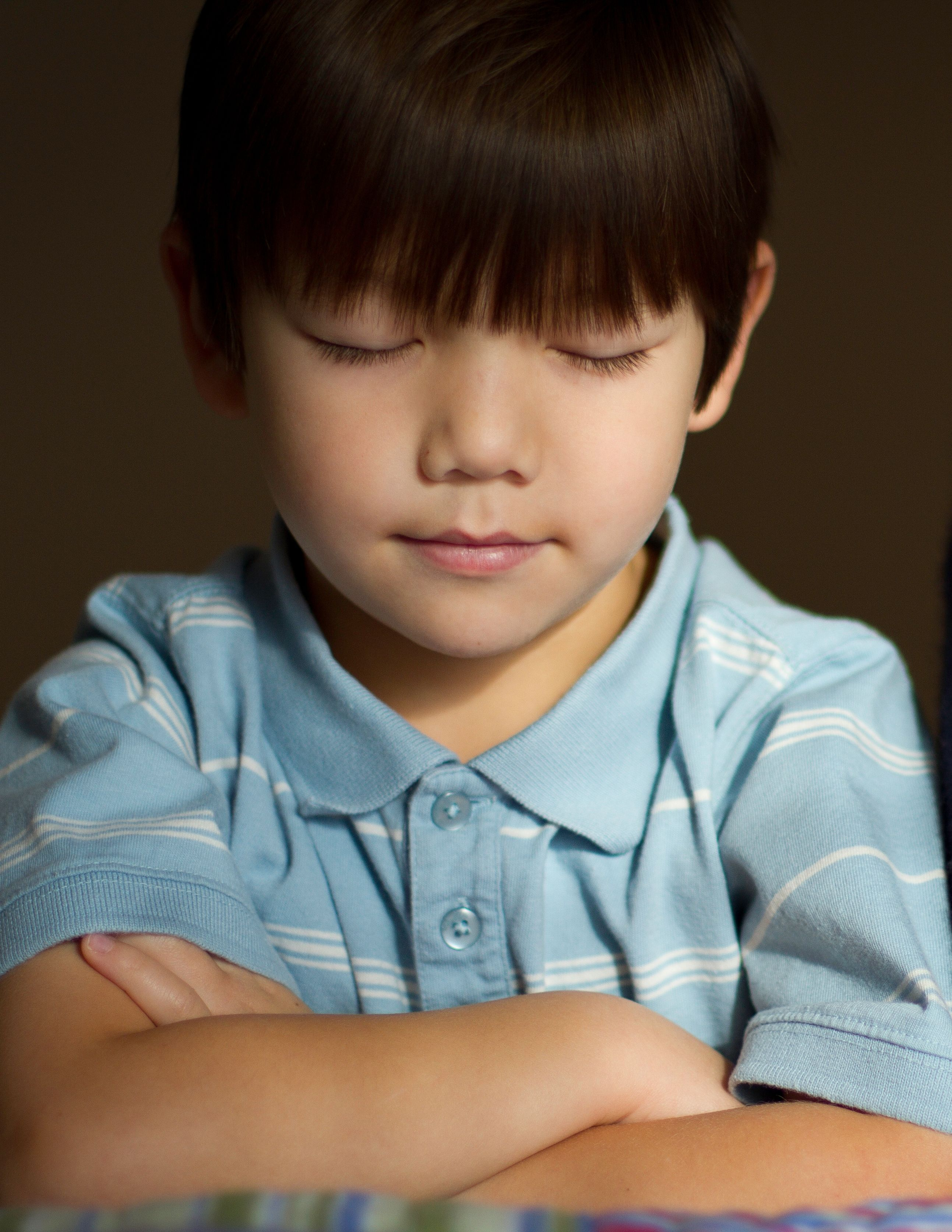 A boy kneeling by his bed with his eyes closed and arms folded in prayer.