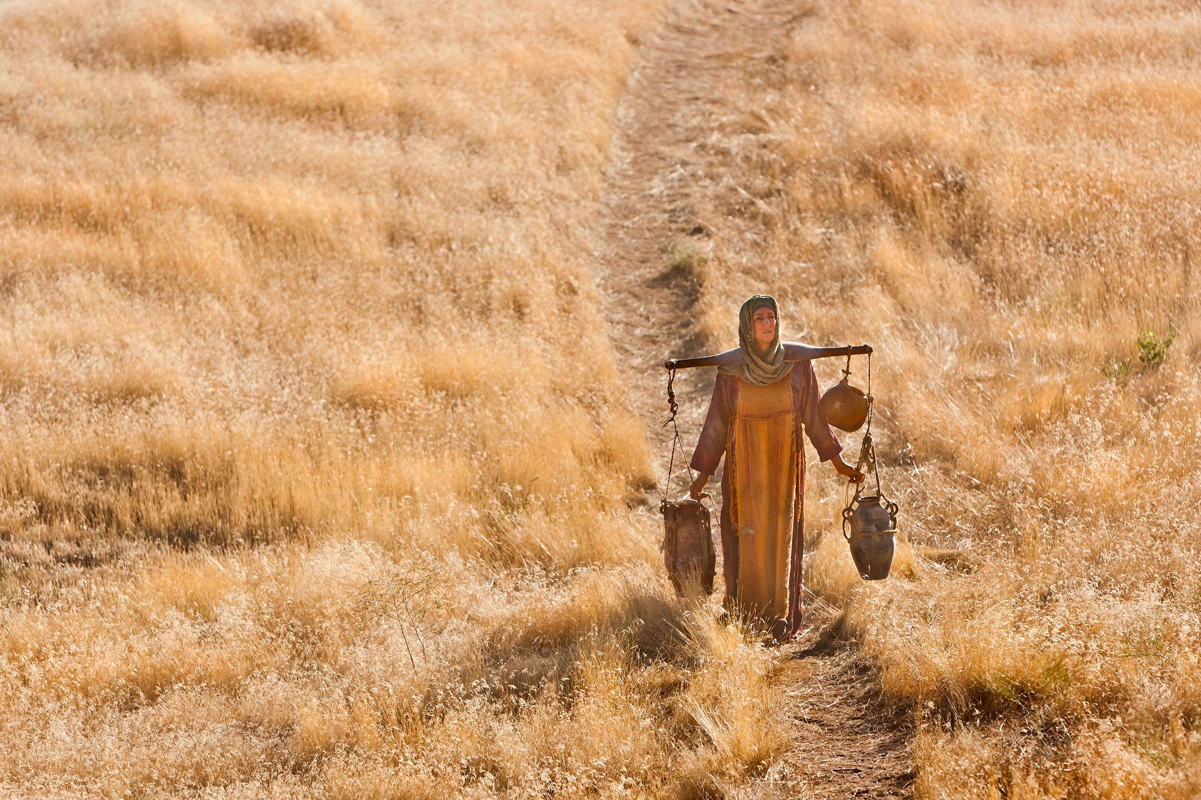 The Samaritan woman carries water from the well after learning from Jesus.