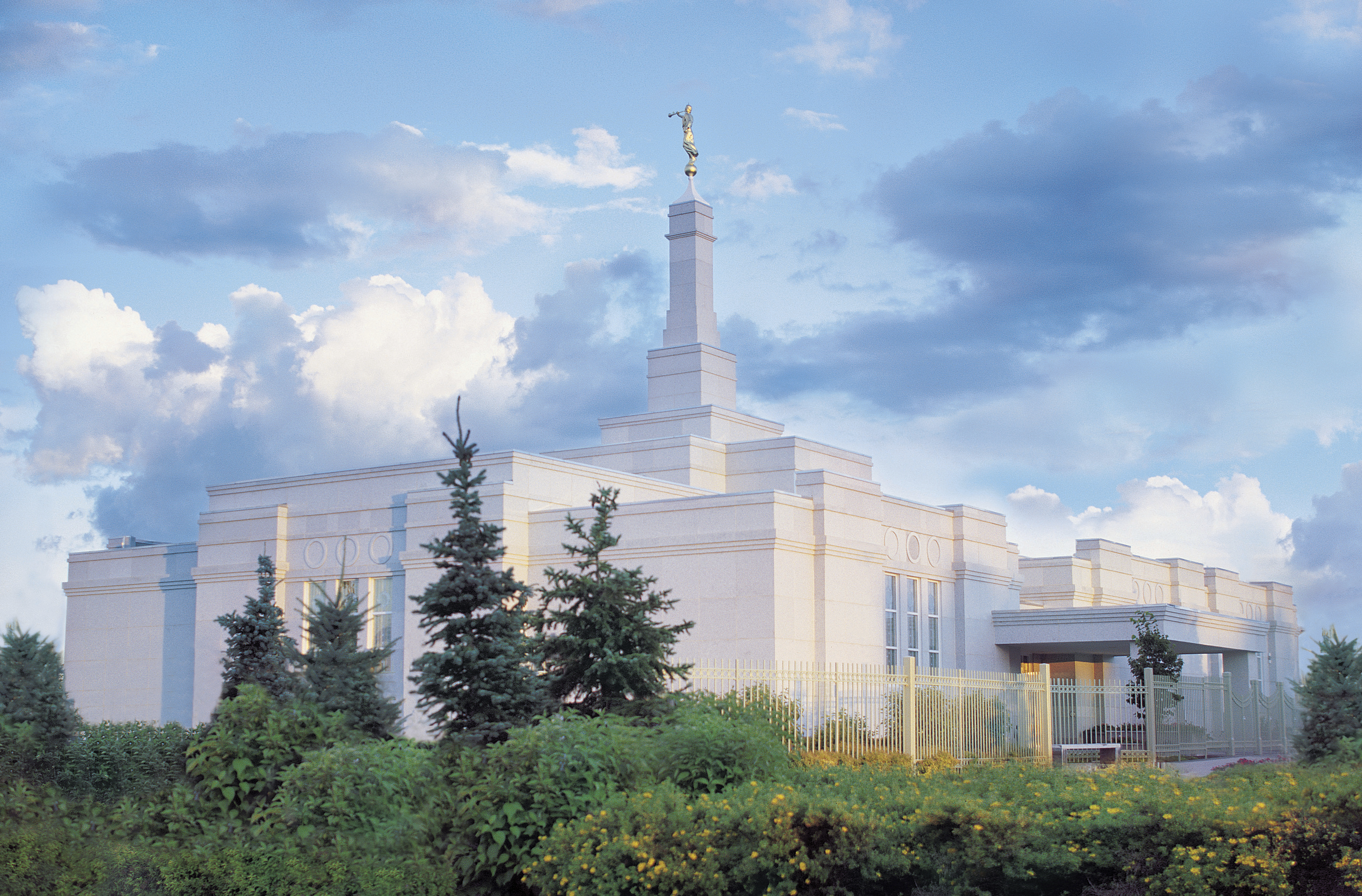 The Regina Saskatchewan Temple, with bushes and evergreen trees growing nearby.