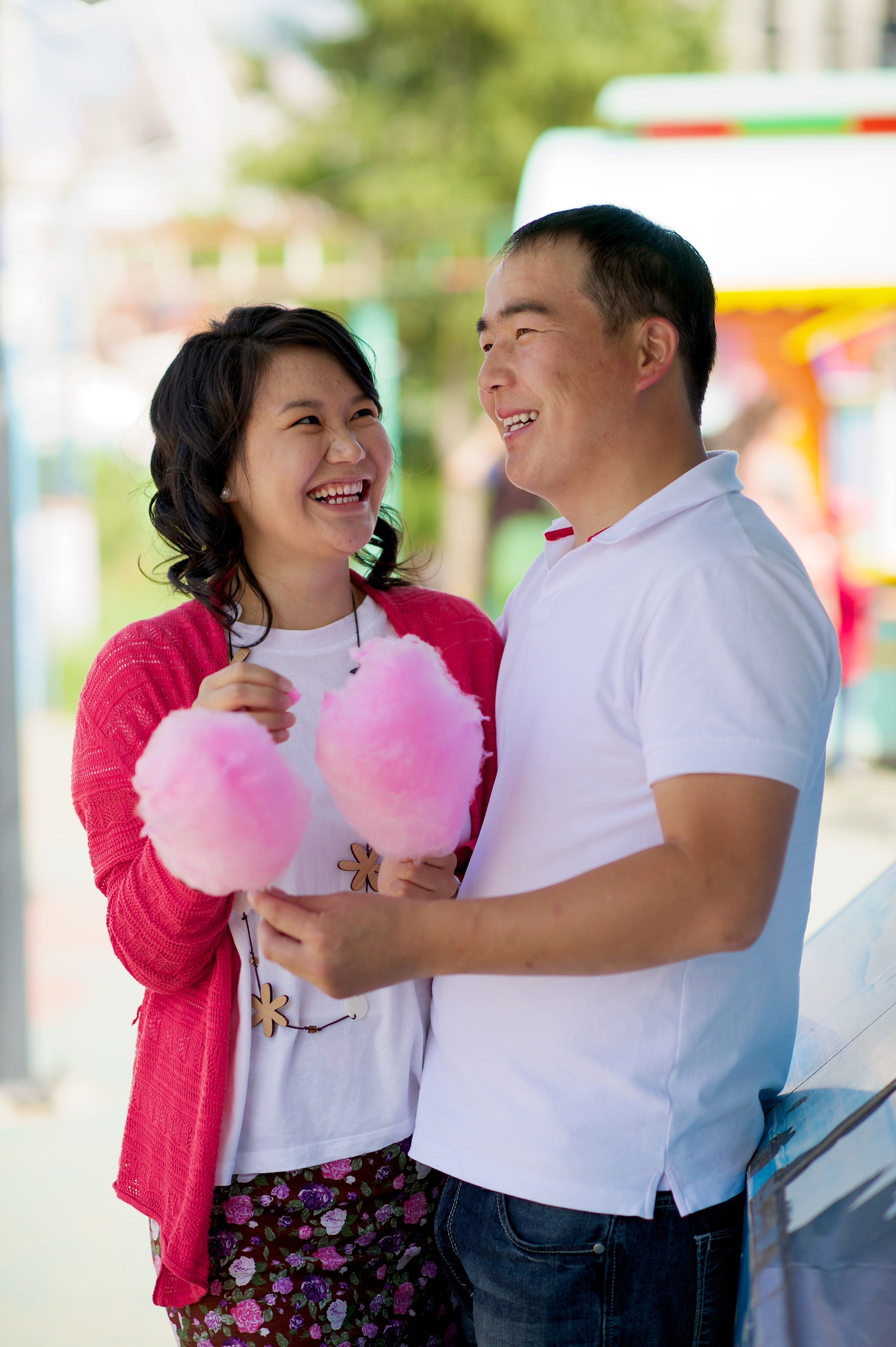 A couple at a carnival, holding cotton candy.