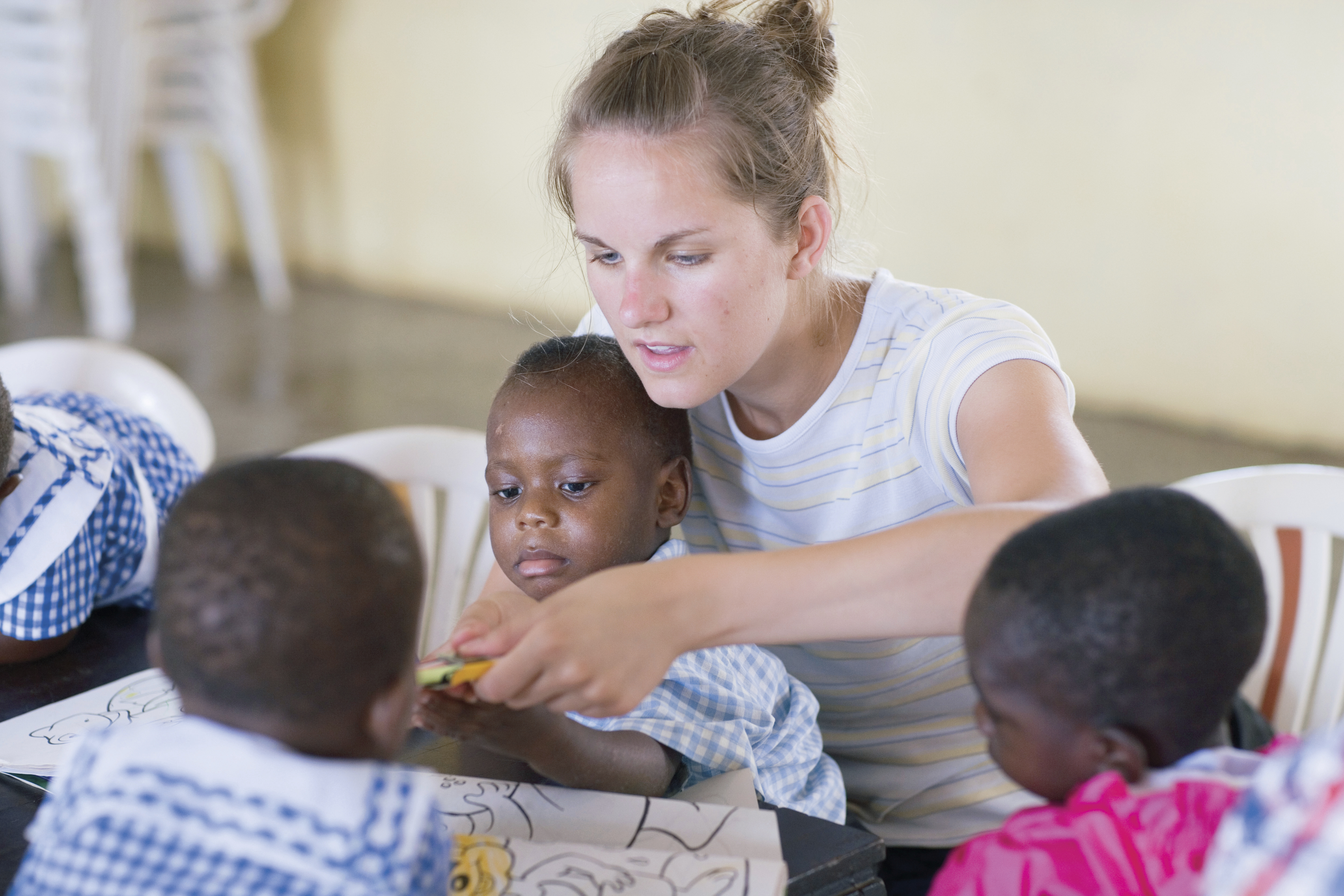 A woman sitting at a table in an orphanage and coloring pictures with three African children.