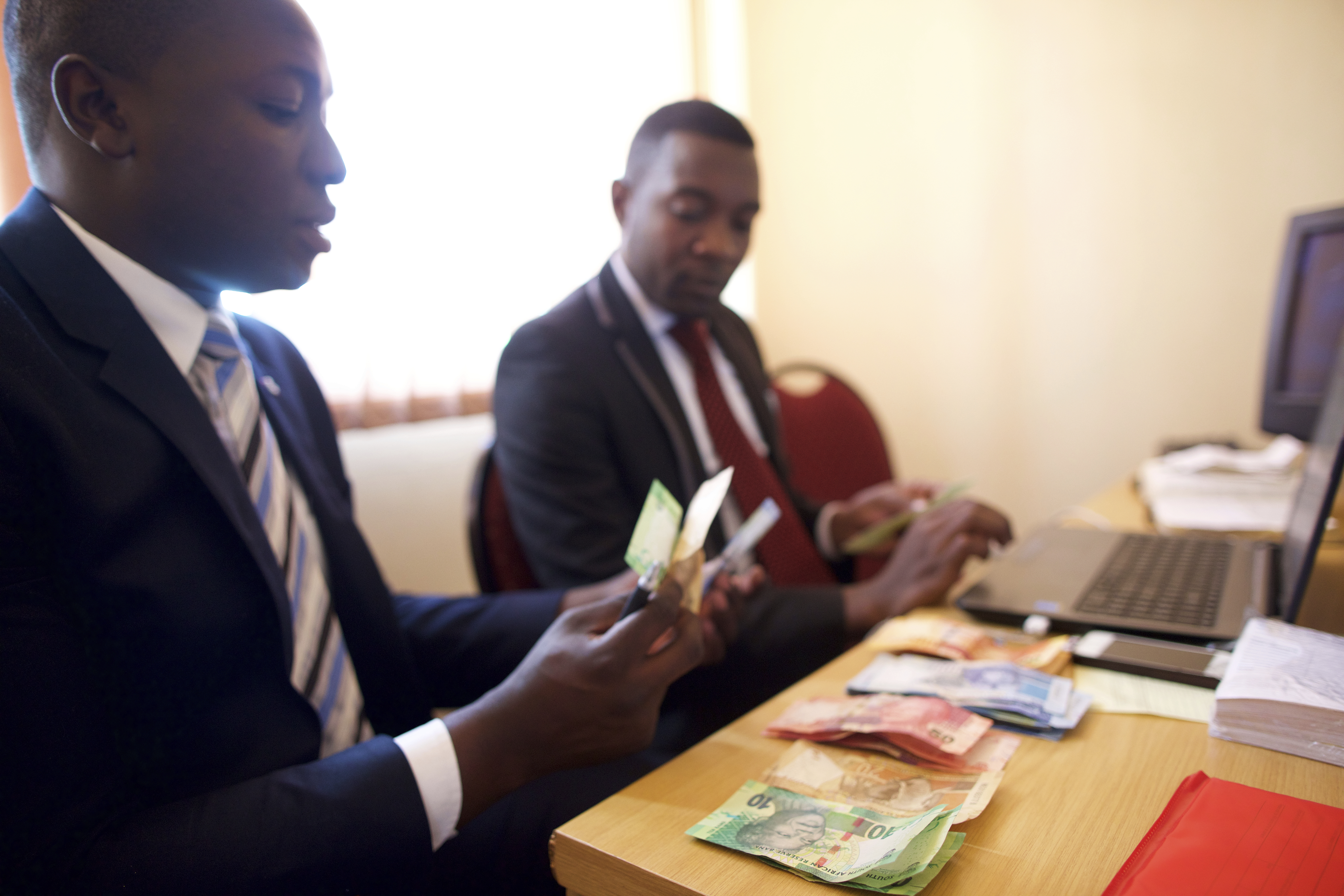 Two ward clerks in South Africa counting rands given for tithes and offerings.