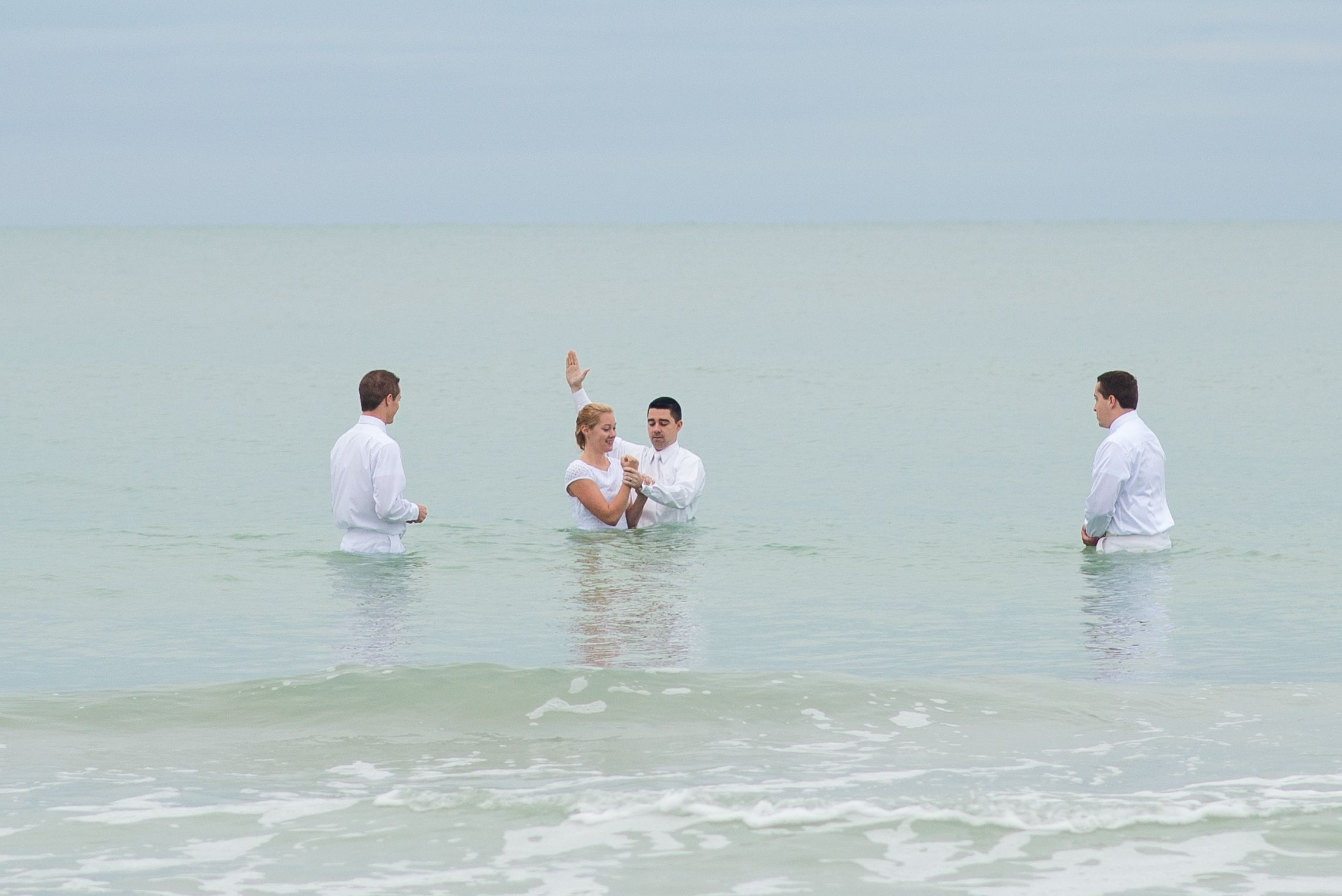 A young woman being baptized in the ocean.