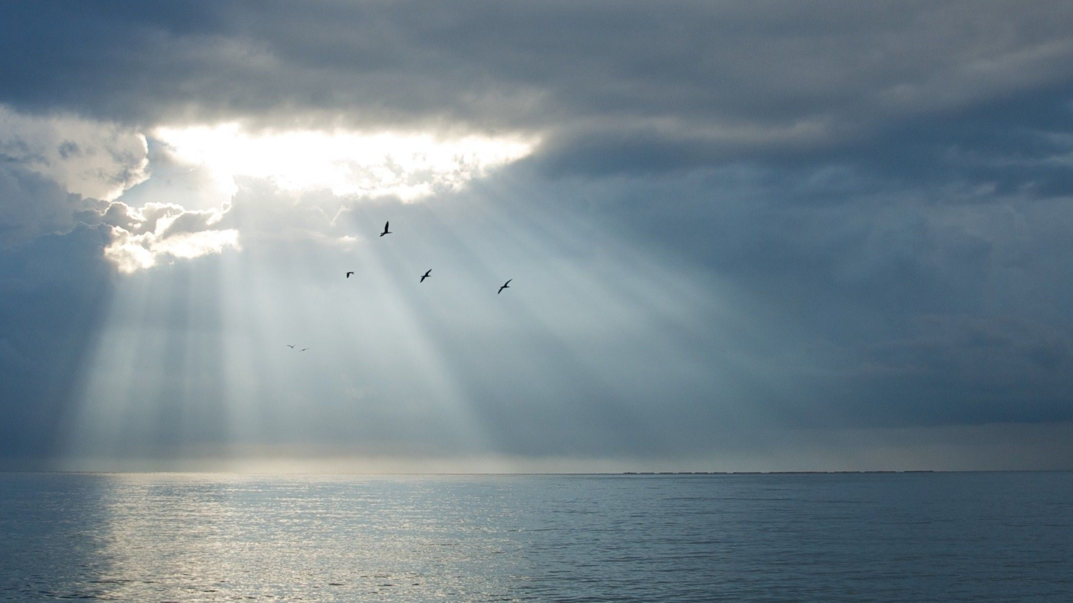 Sun rays break through a hole in a layer of clouds over the ocean.