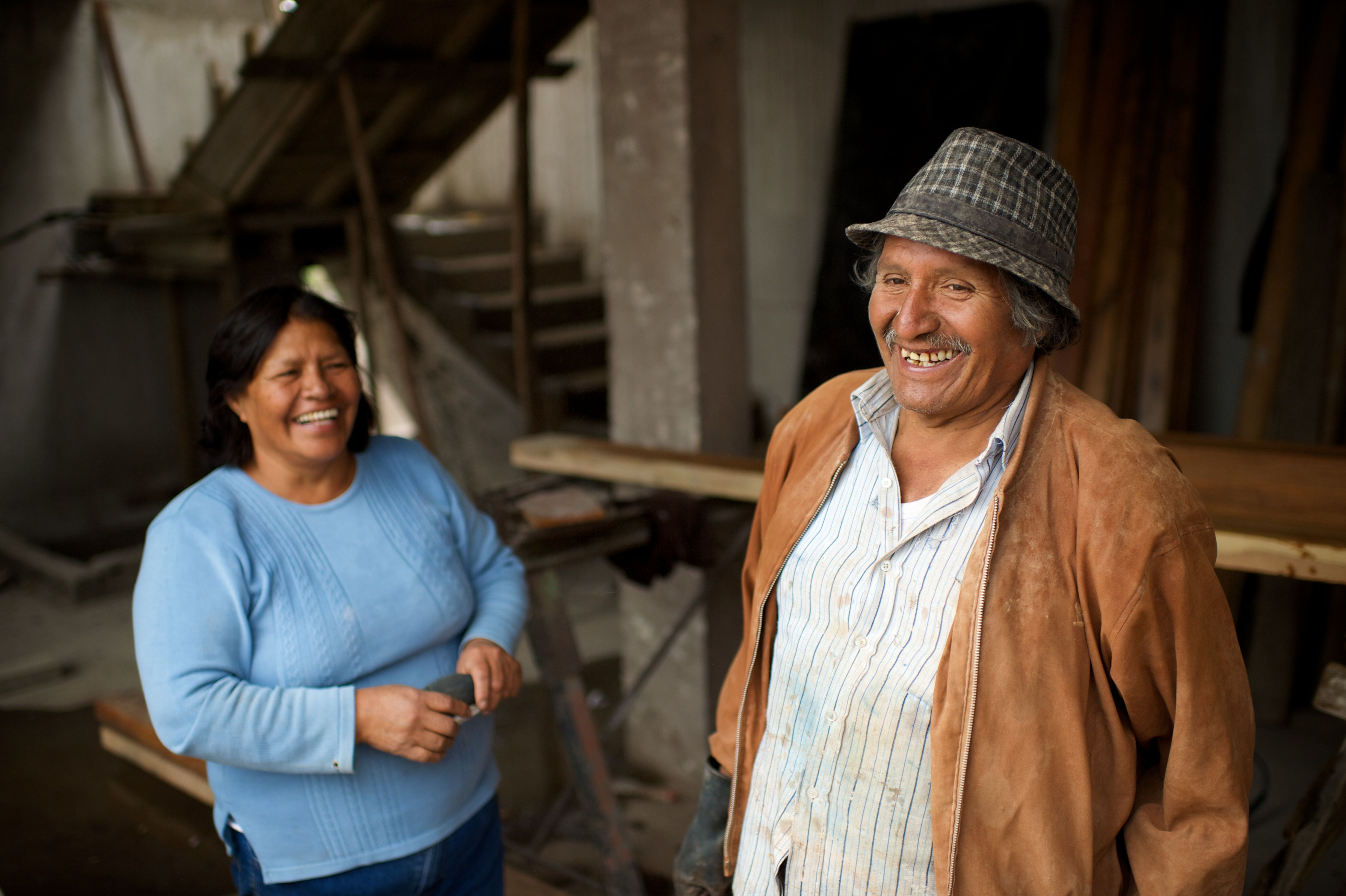 A couple from Ecuador laughing and standing in a workshop.