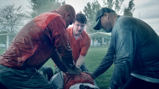Three men give an injured man a priesthood blessing in the rain on a field