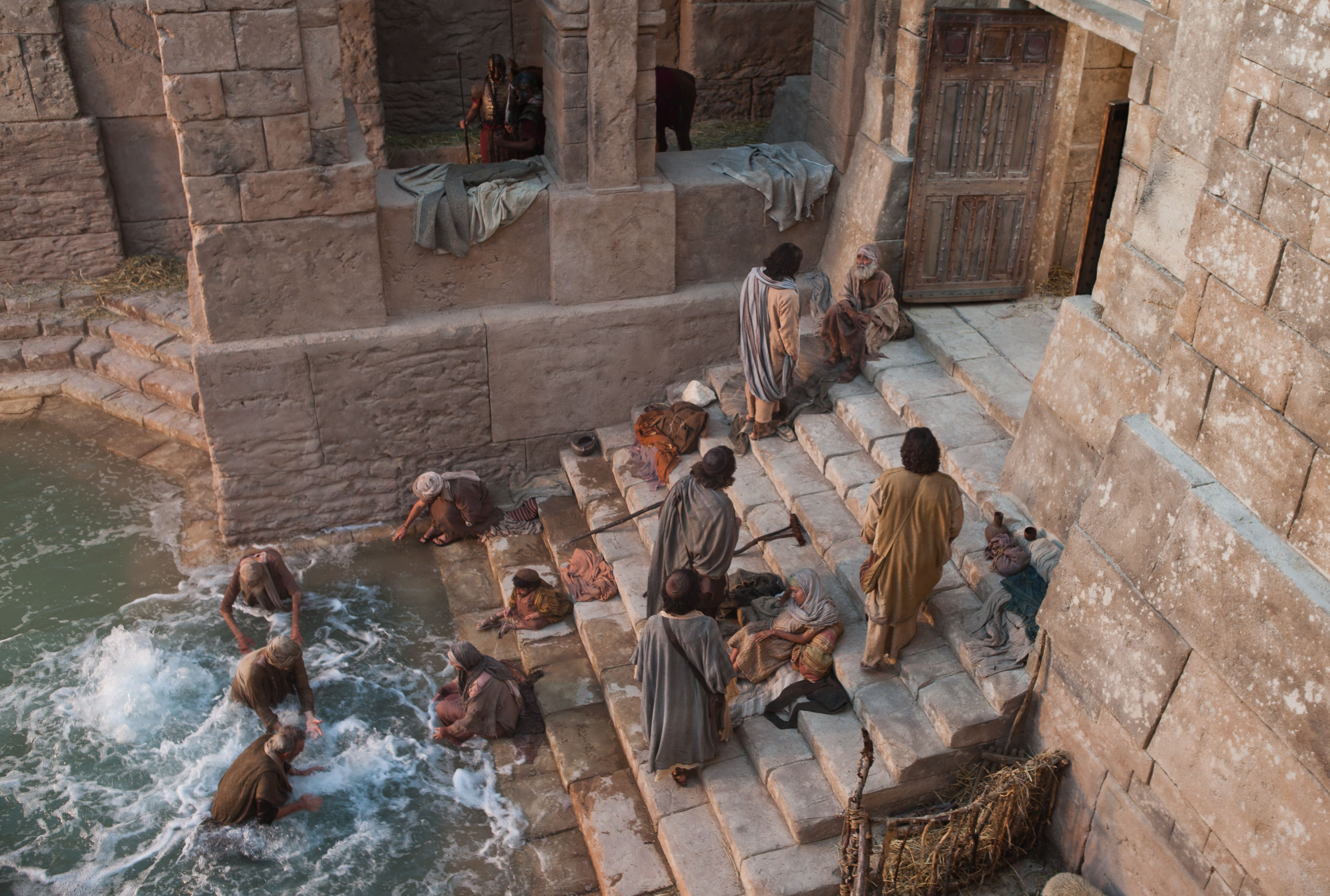 A group of people at the pool of Bethesda trying to be first to enter the water.