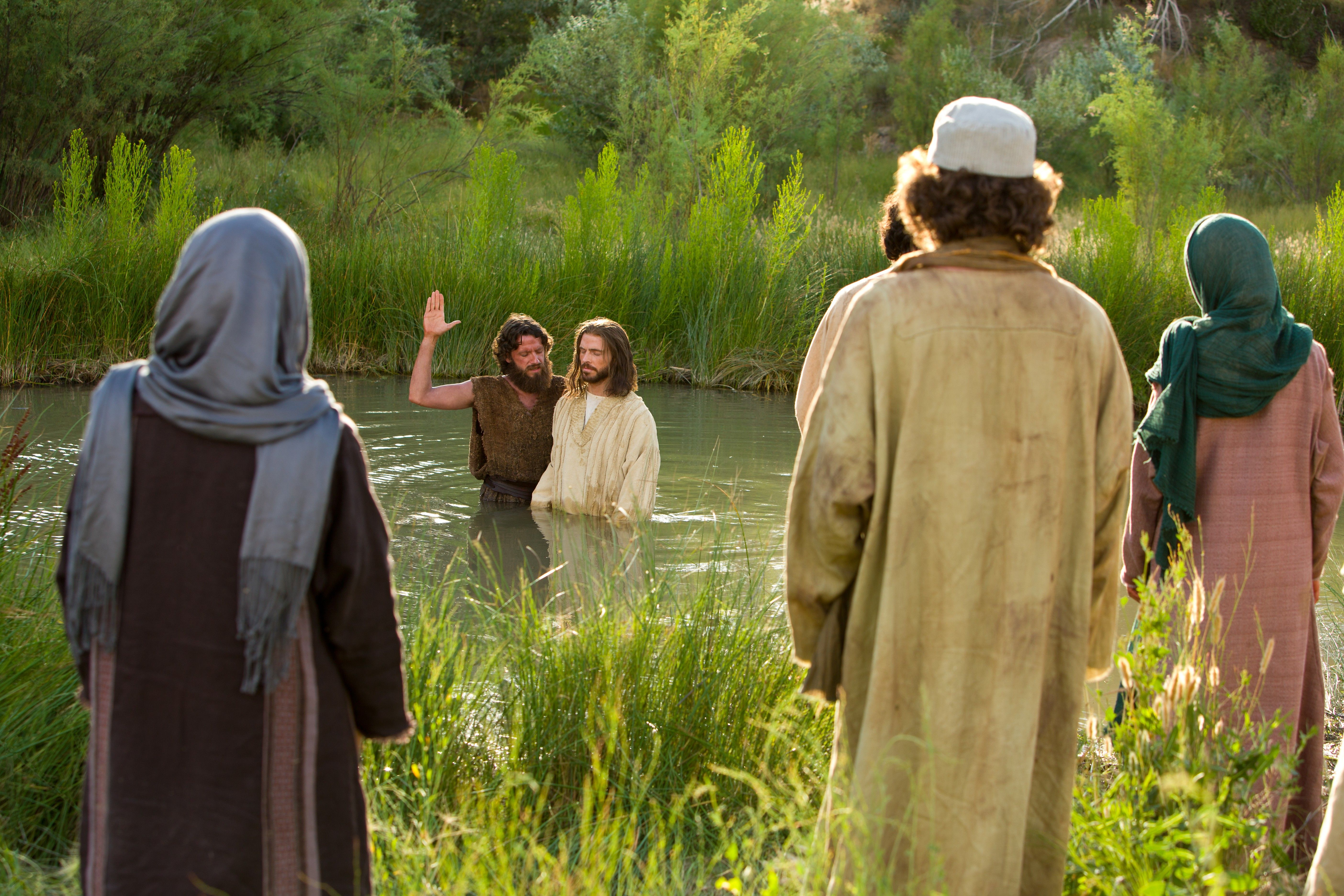 John the Baptist baptizes the Savior in the River Jordan as others look on.