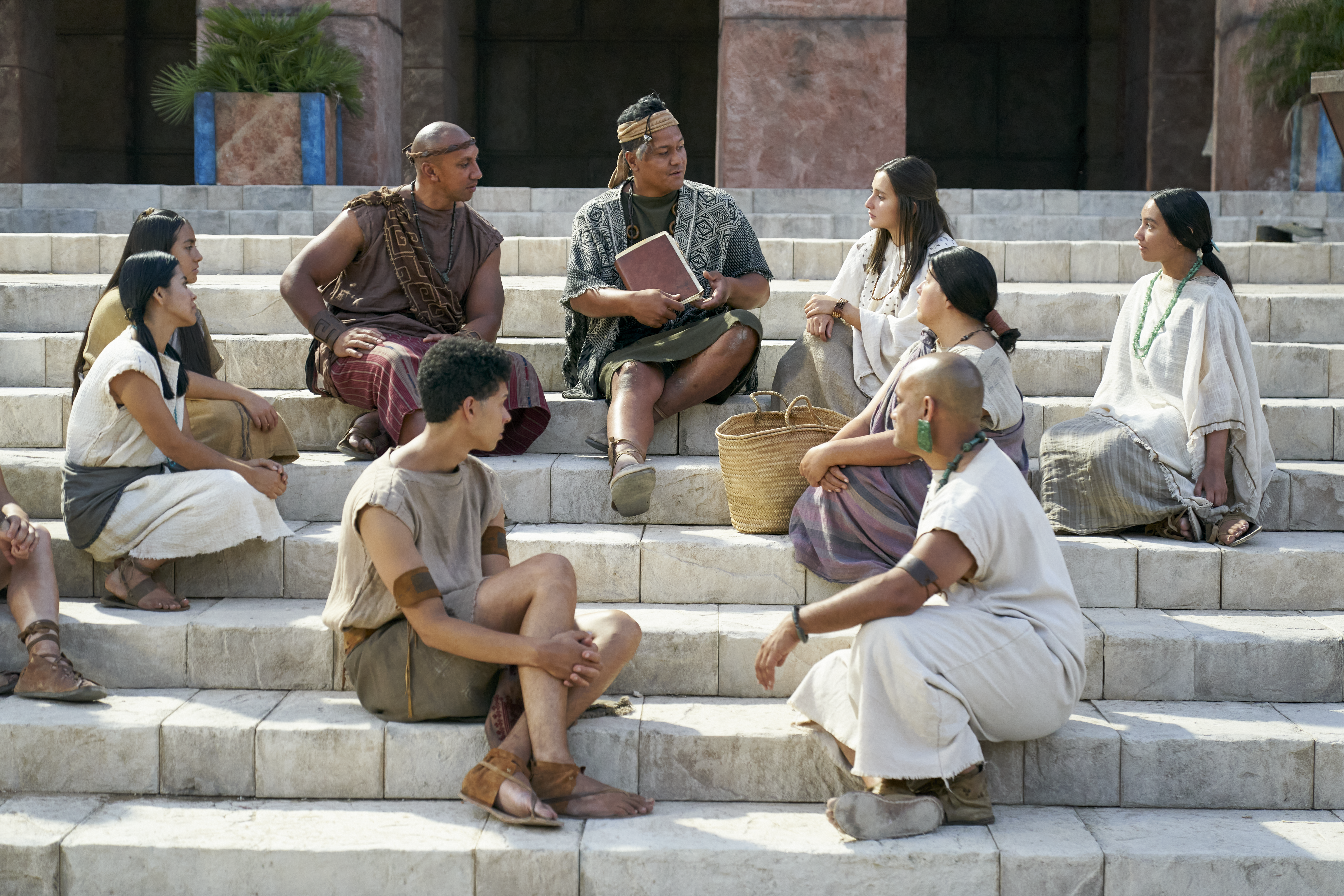 People gather to learn on the steps of the city as a man teaches in the city of Zarahemla.