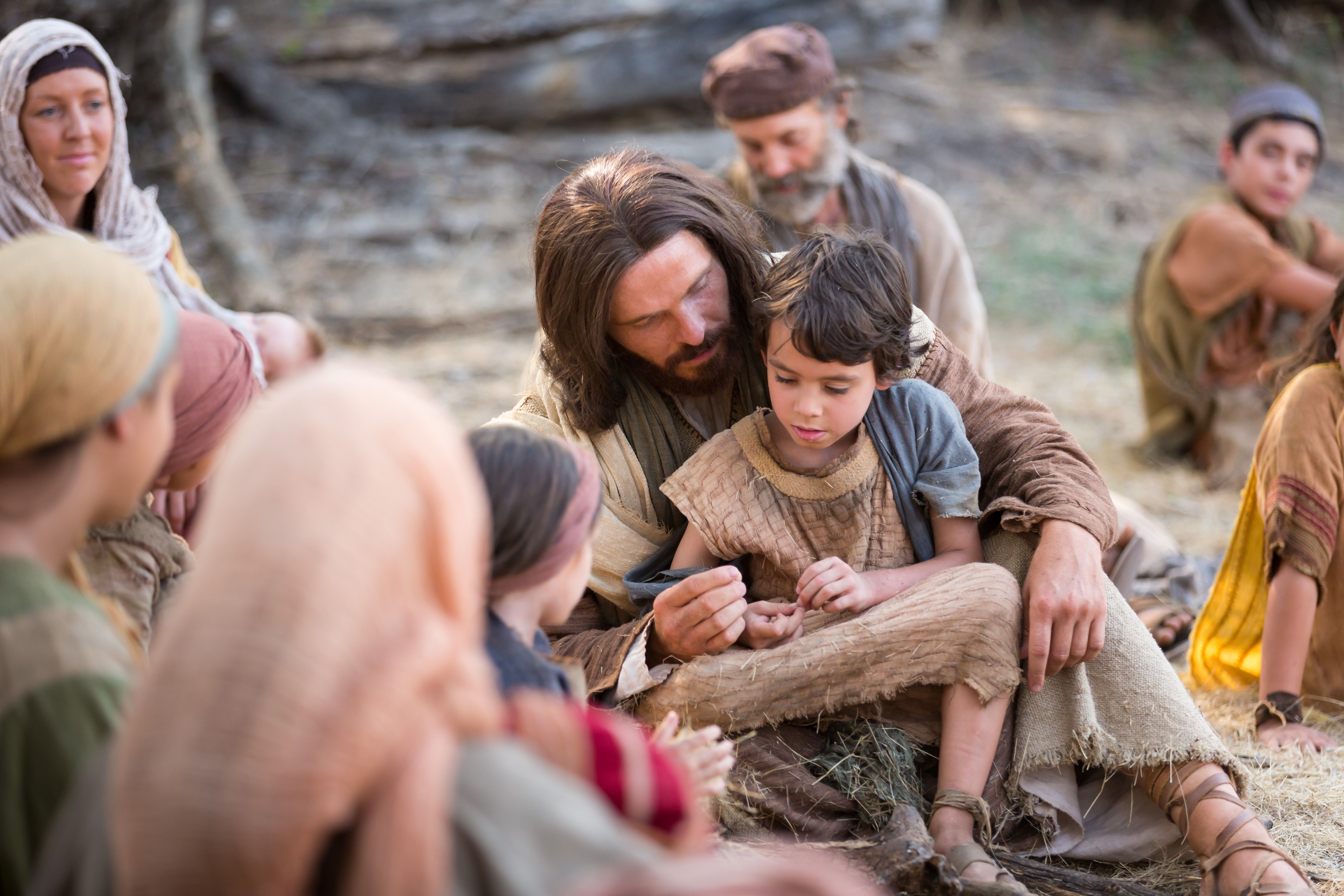 """Jesus sits with a young child after telling His Apostles, """"Suffer little children to come unto me."""""""