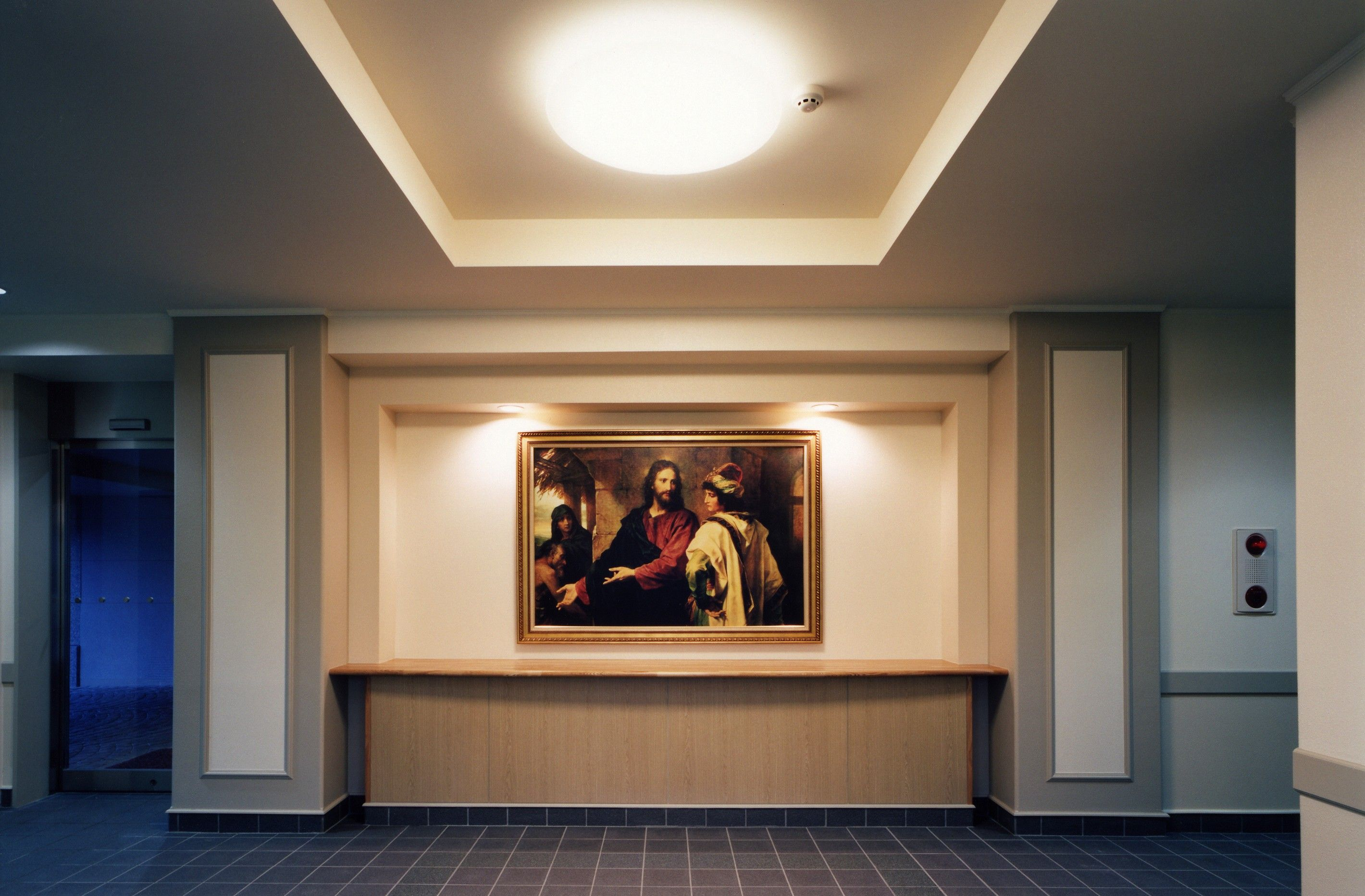 A meetinghouse foyer with a light shining on a painting of Christ.