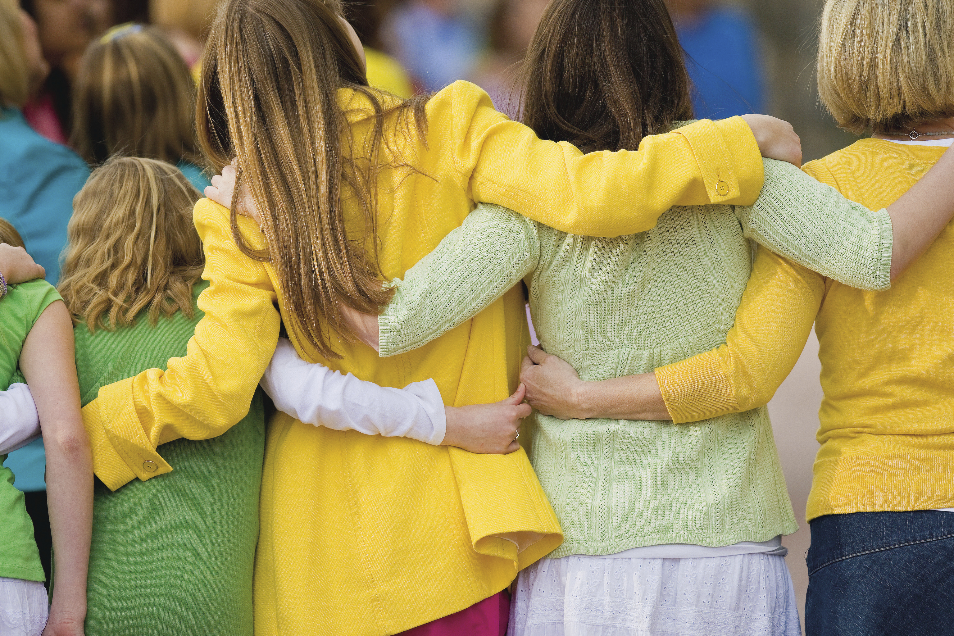A line of women of different ages linking arms to form a chain.