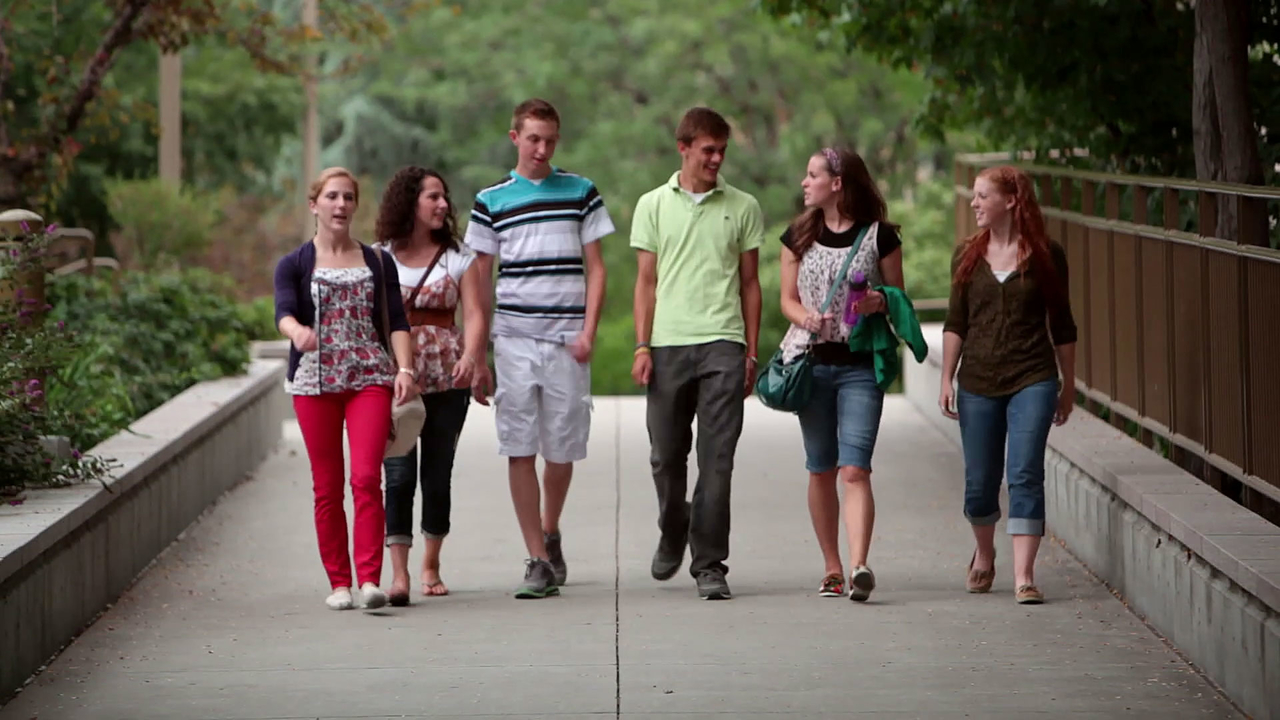 A group of 6 teenagers walk on a sidewalk surrounded by trees
