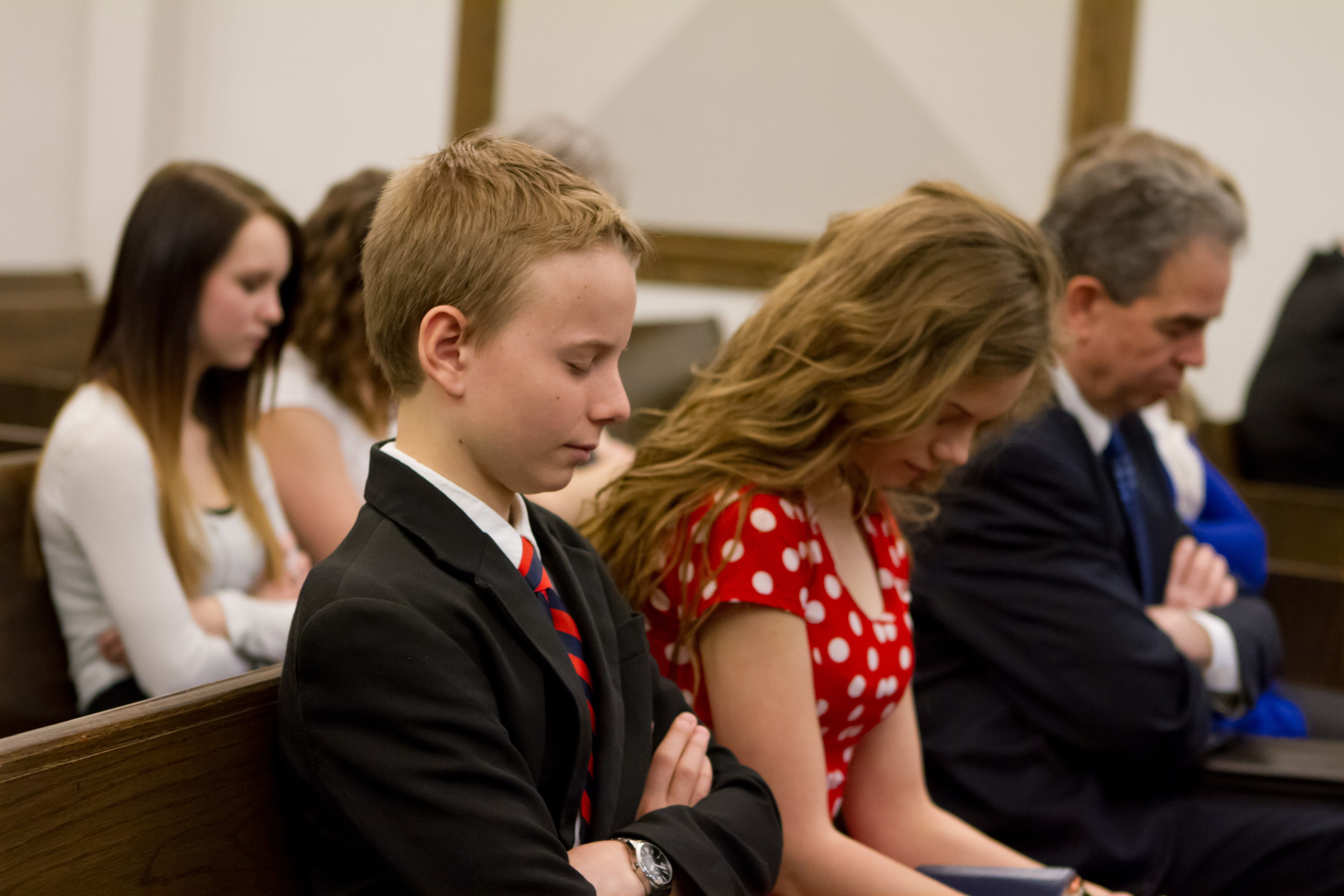 A family bow their heads during prayer in sacrament meeting.