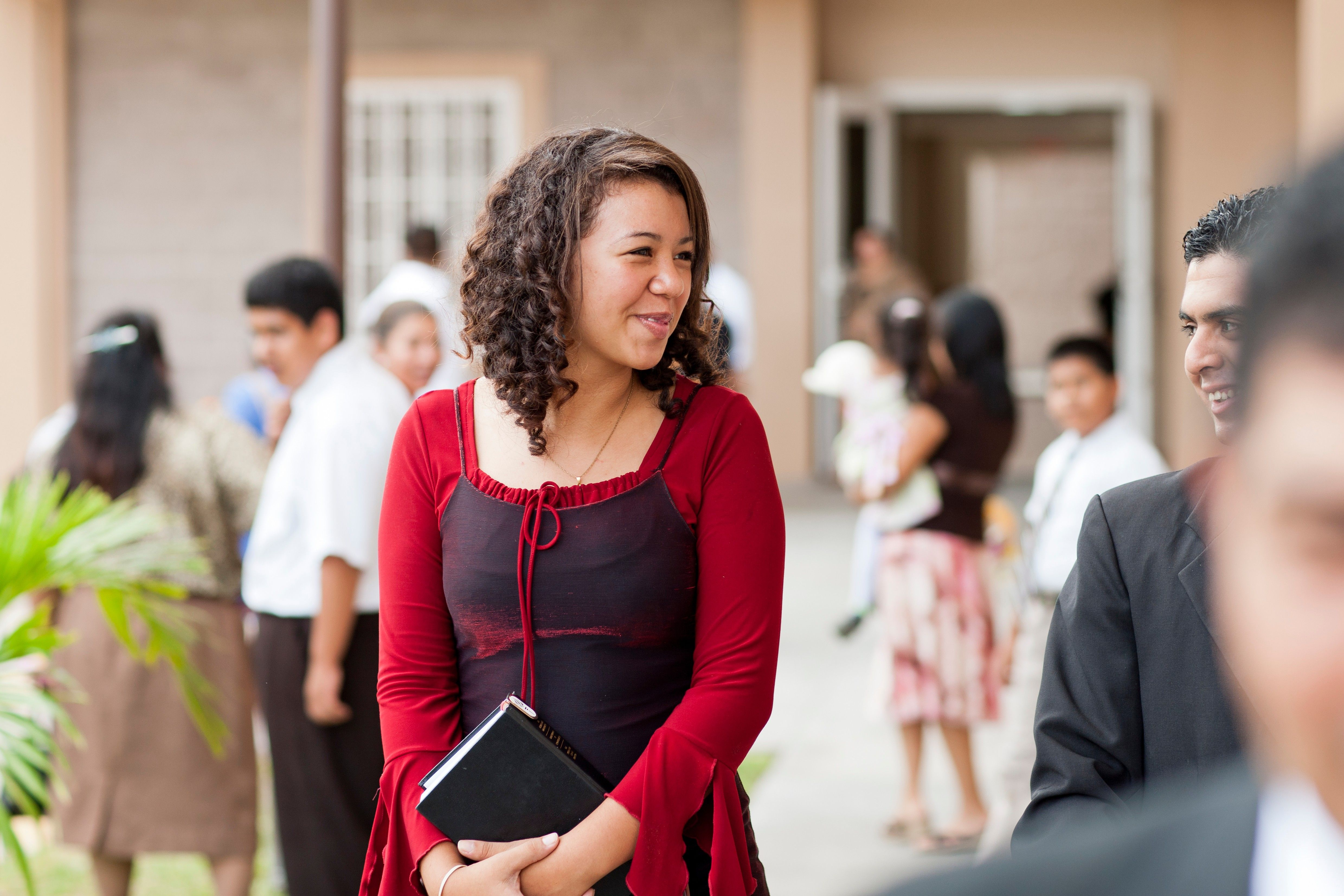 A portrait of a young woman holding scriptures outside a Church building in El Salvador.
