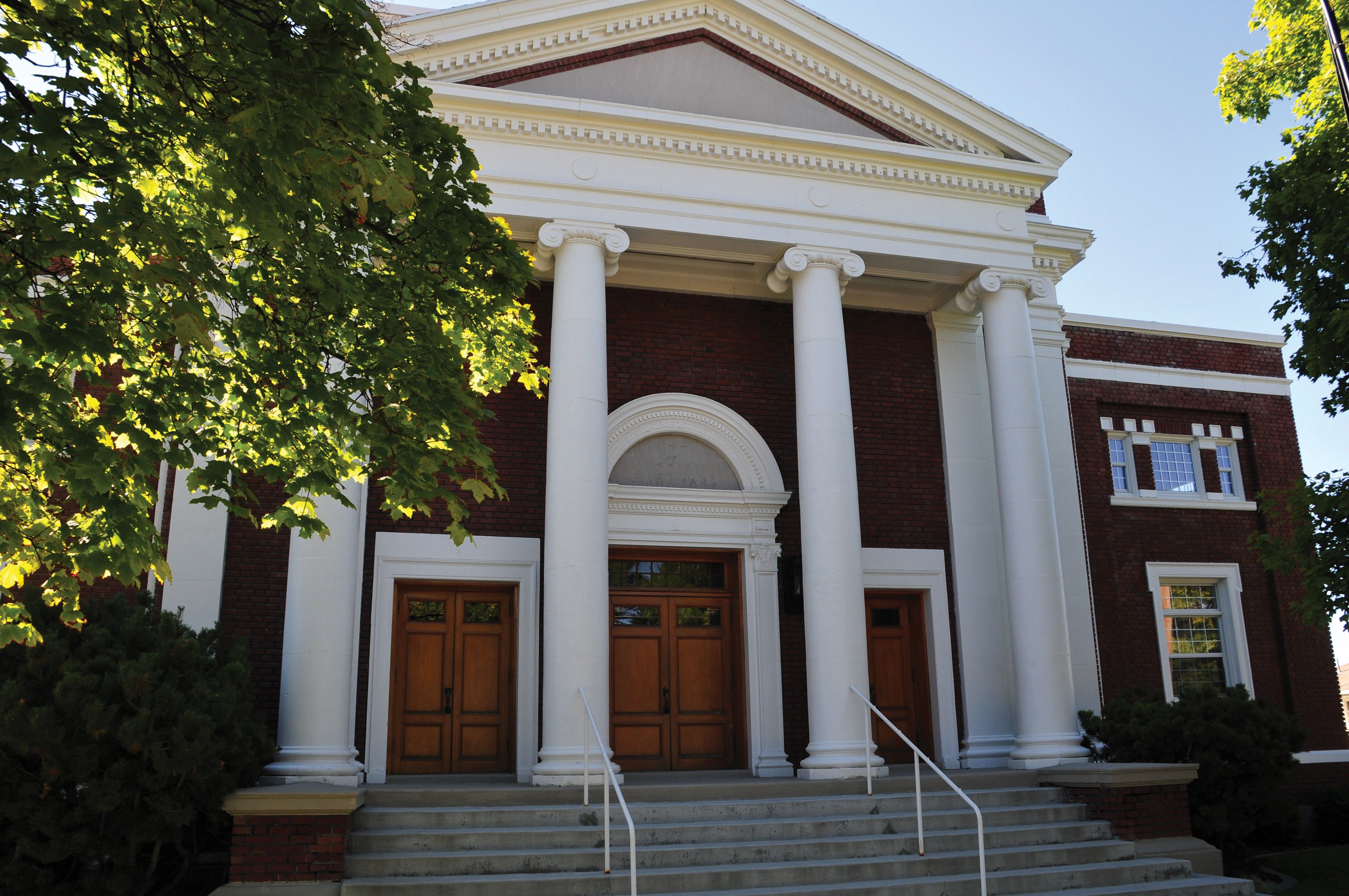 The outside of a chapel in Logan, Utah, showing brick, pillars, and stairs.