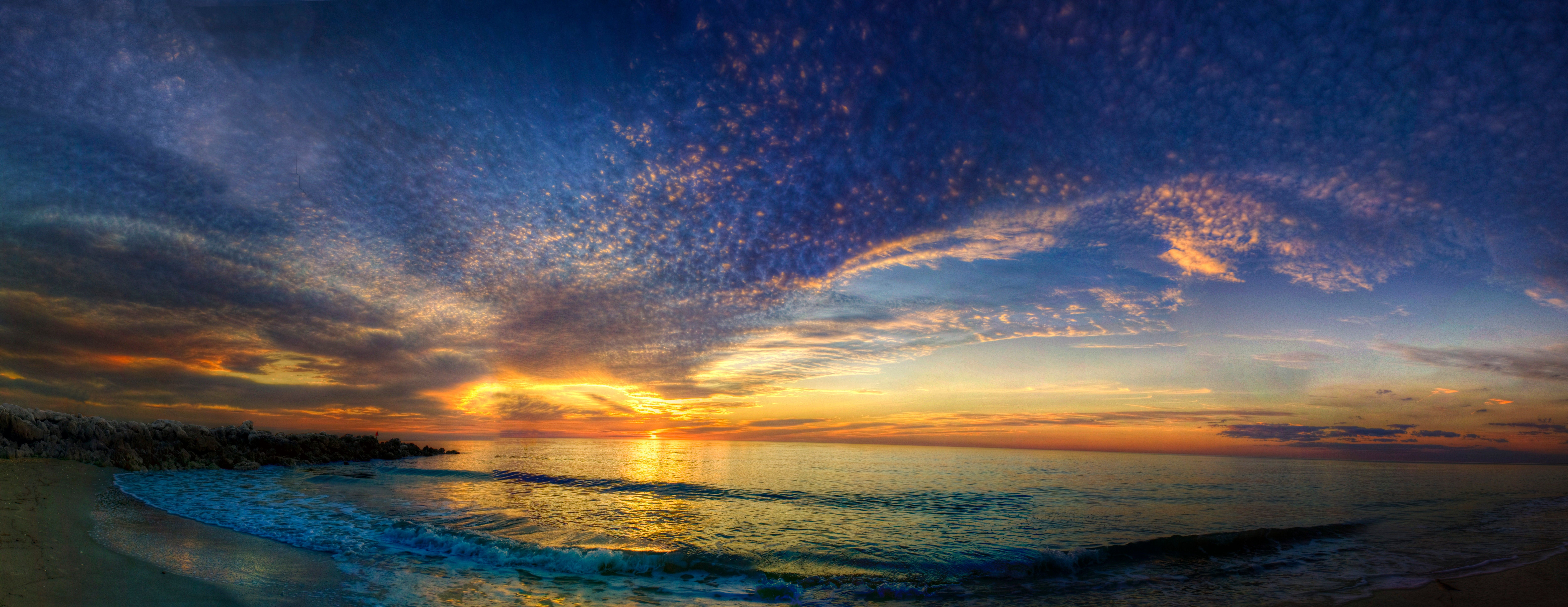 A panorama of the sun setting over the ocean.