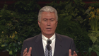 A photo of President Dieter F. Uchtdorf standing at the pulpit in the General Conference Center.