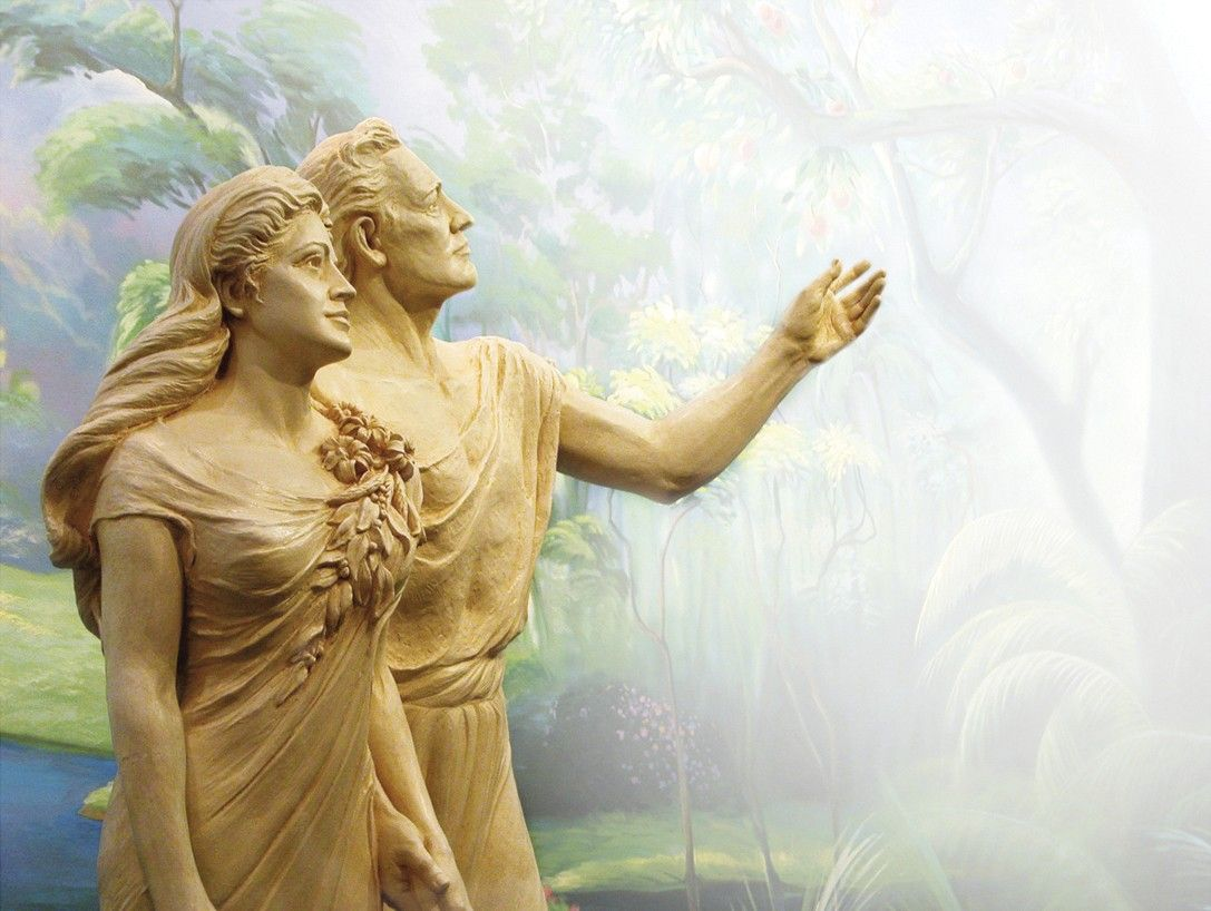A statue of Adam and Eve in front of a mural.