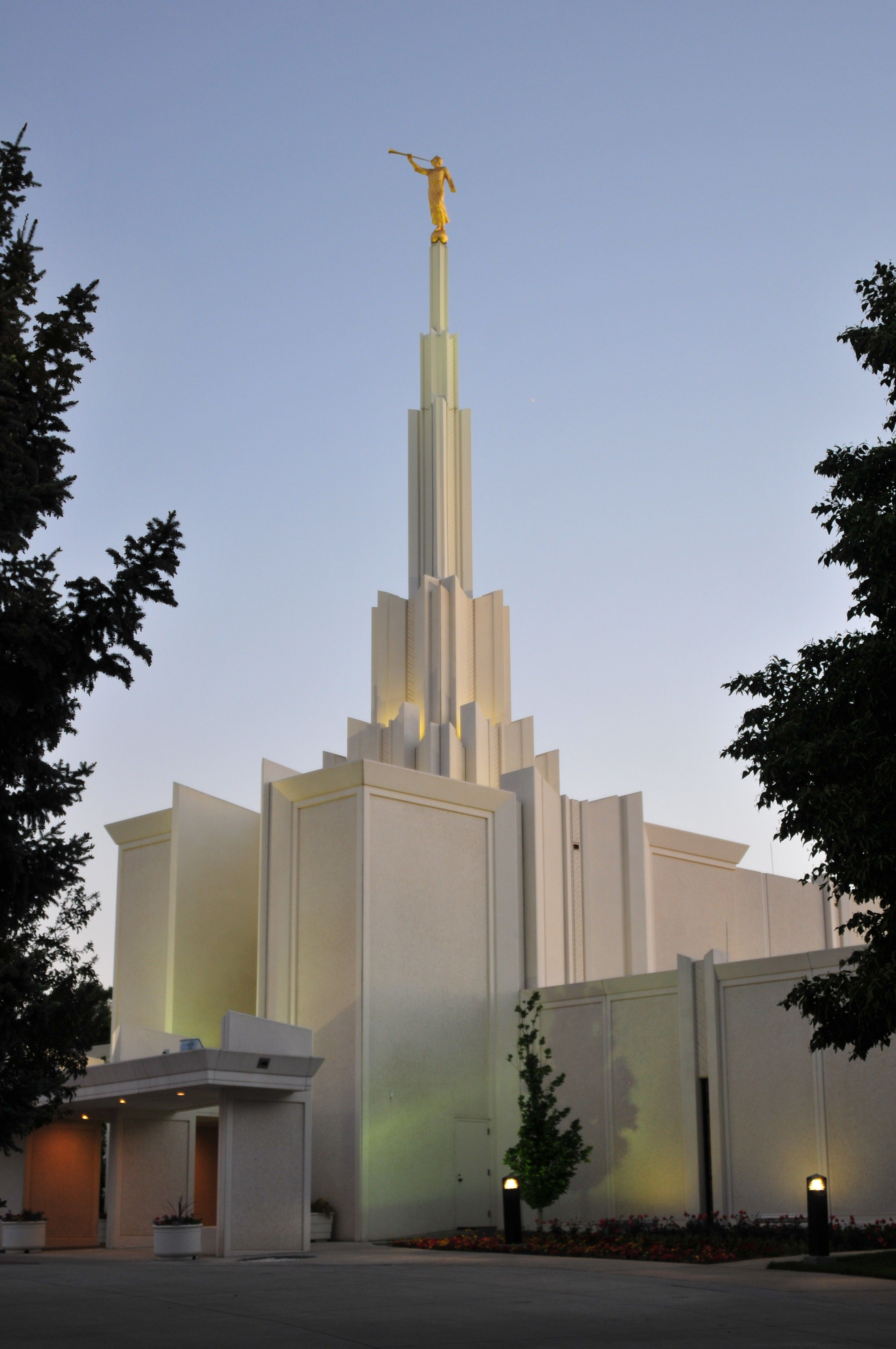 A portrait view of the Denver Colorado Temple lit up at night.