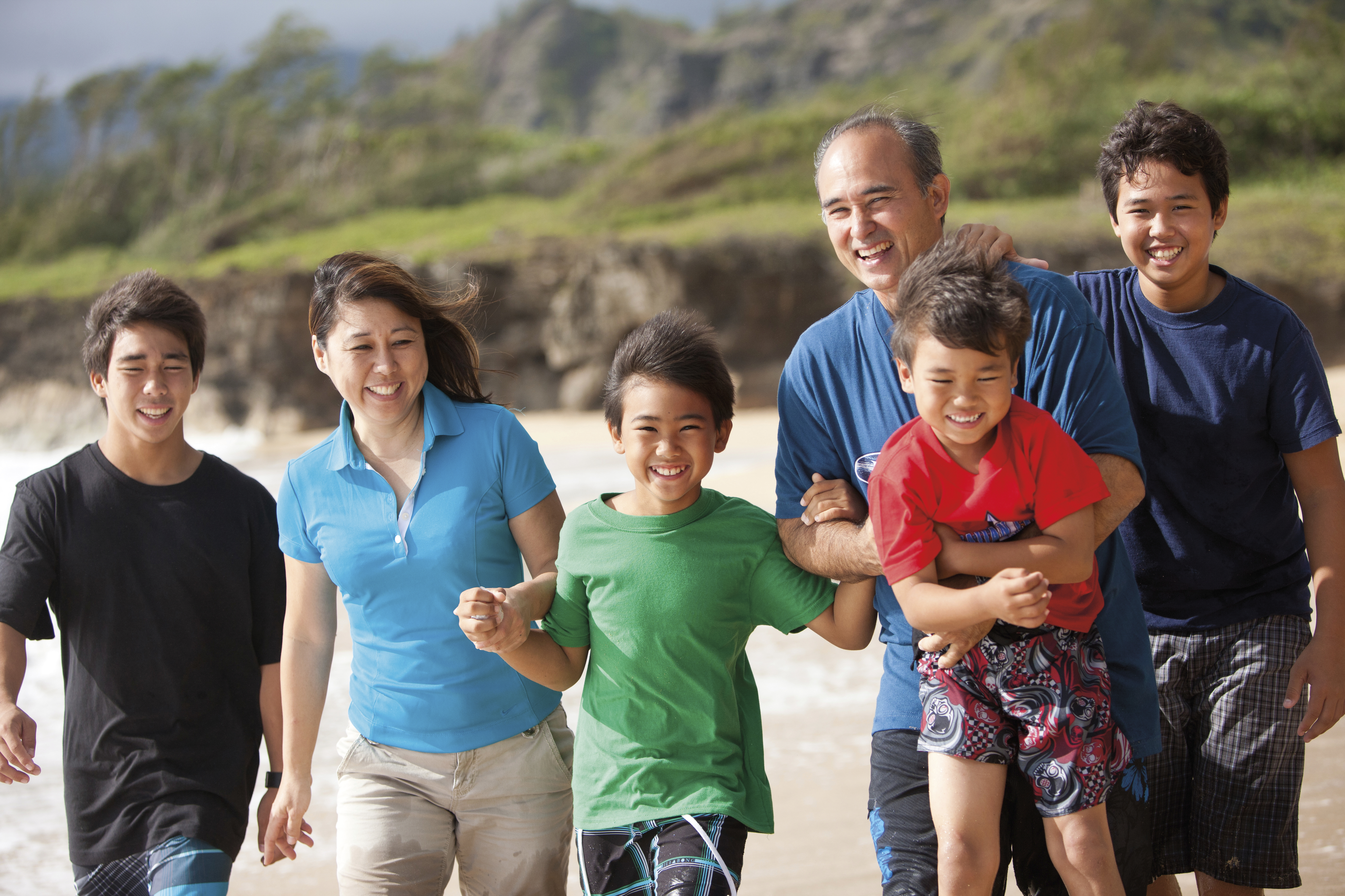 A family in Hawaii walks along the beach together.