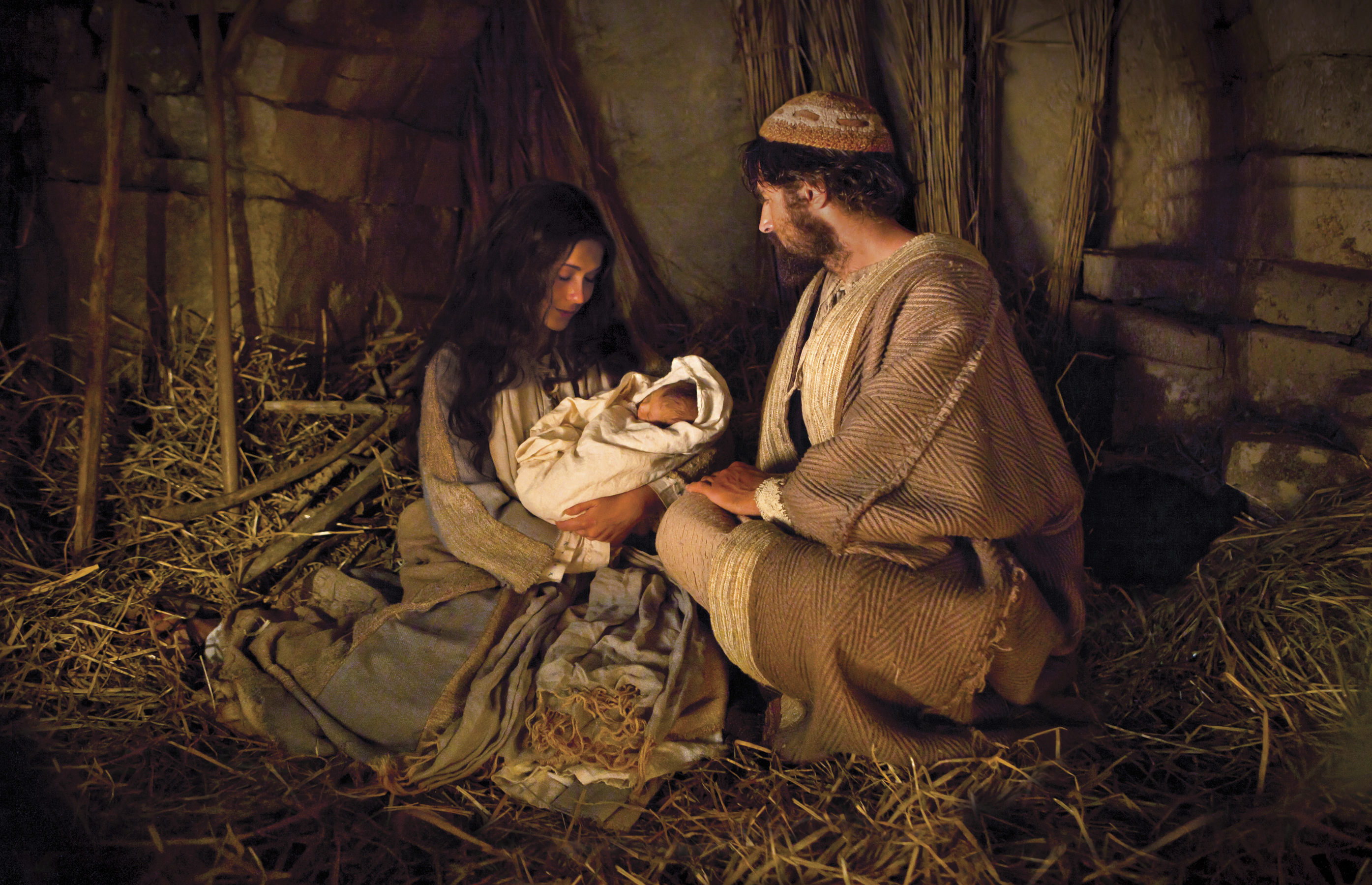 Joseph and Mary hold the baby Jesus on the night of His birth.