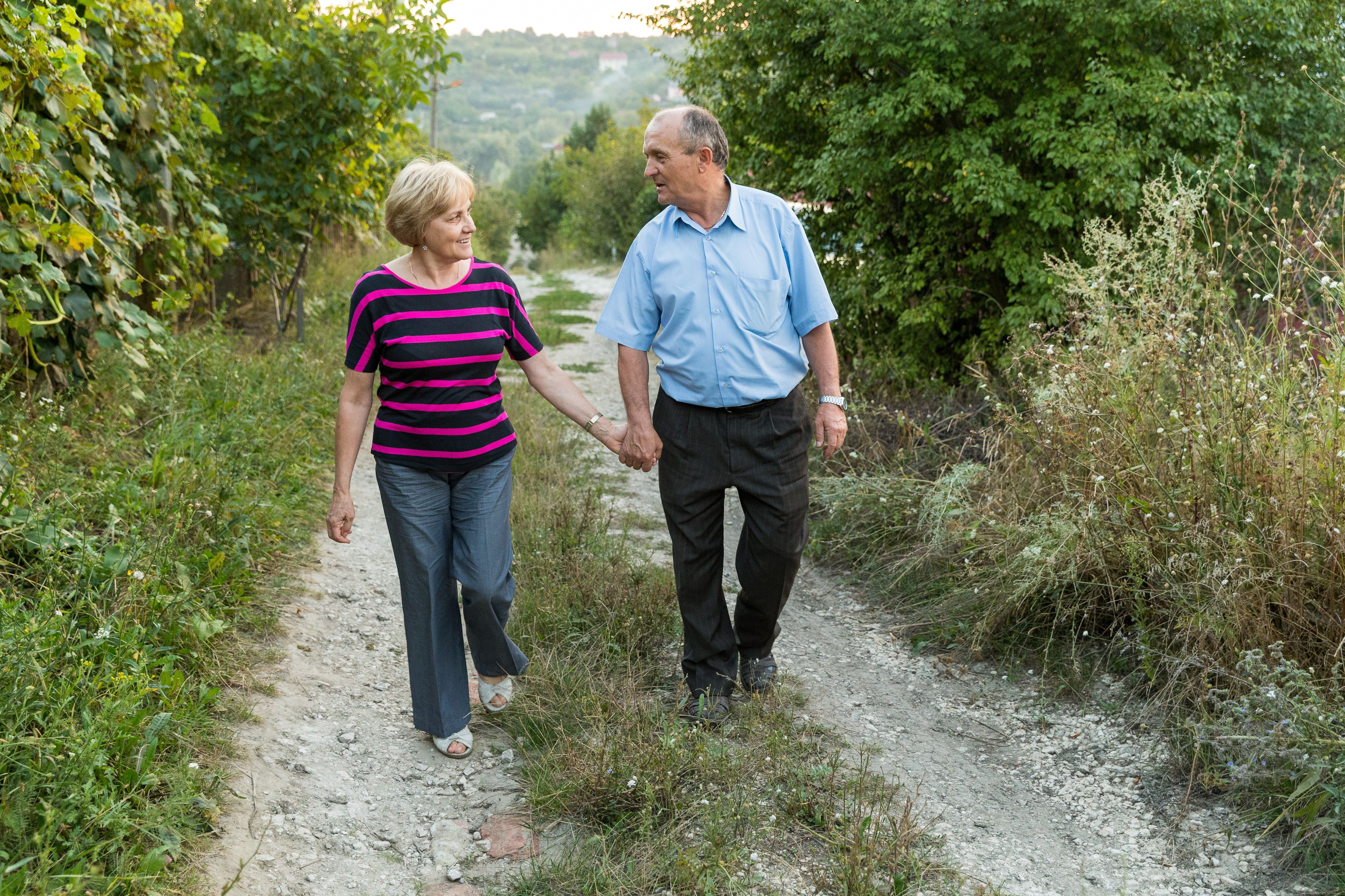An elderly couple from Moldova holding hands and walking on a road together.