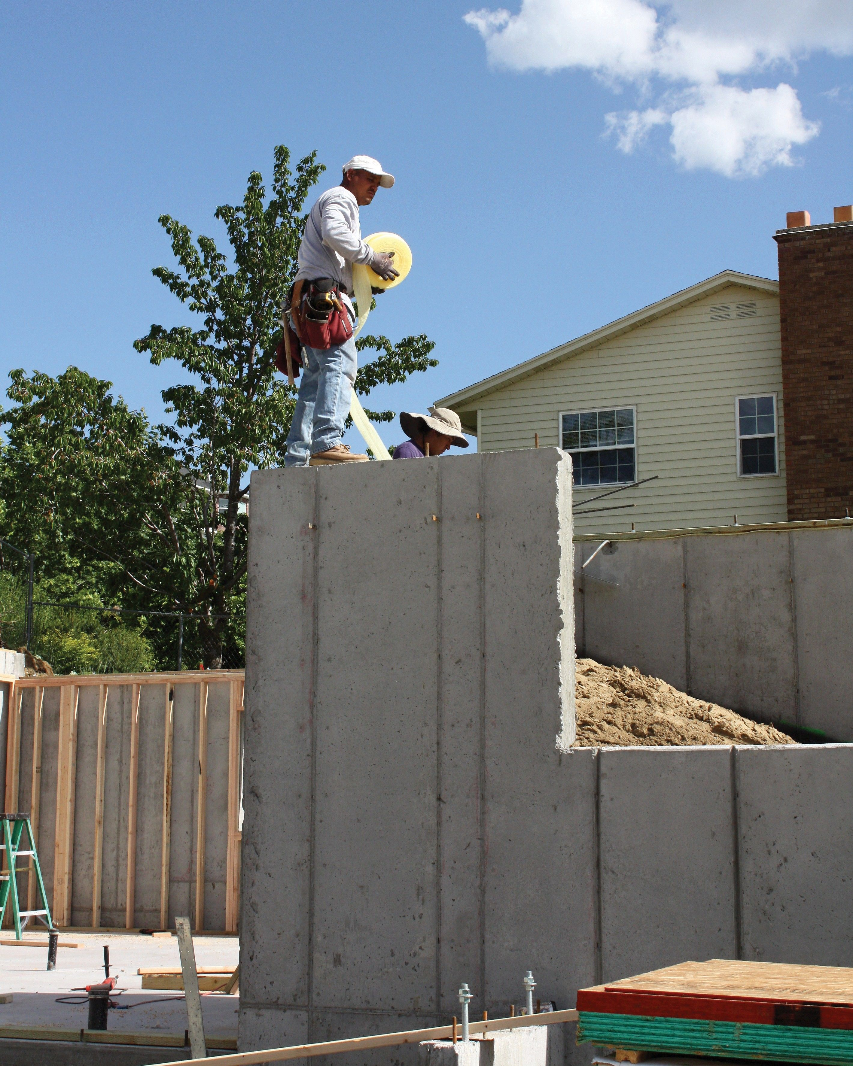 Workers building houses with concrete foundations.