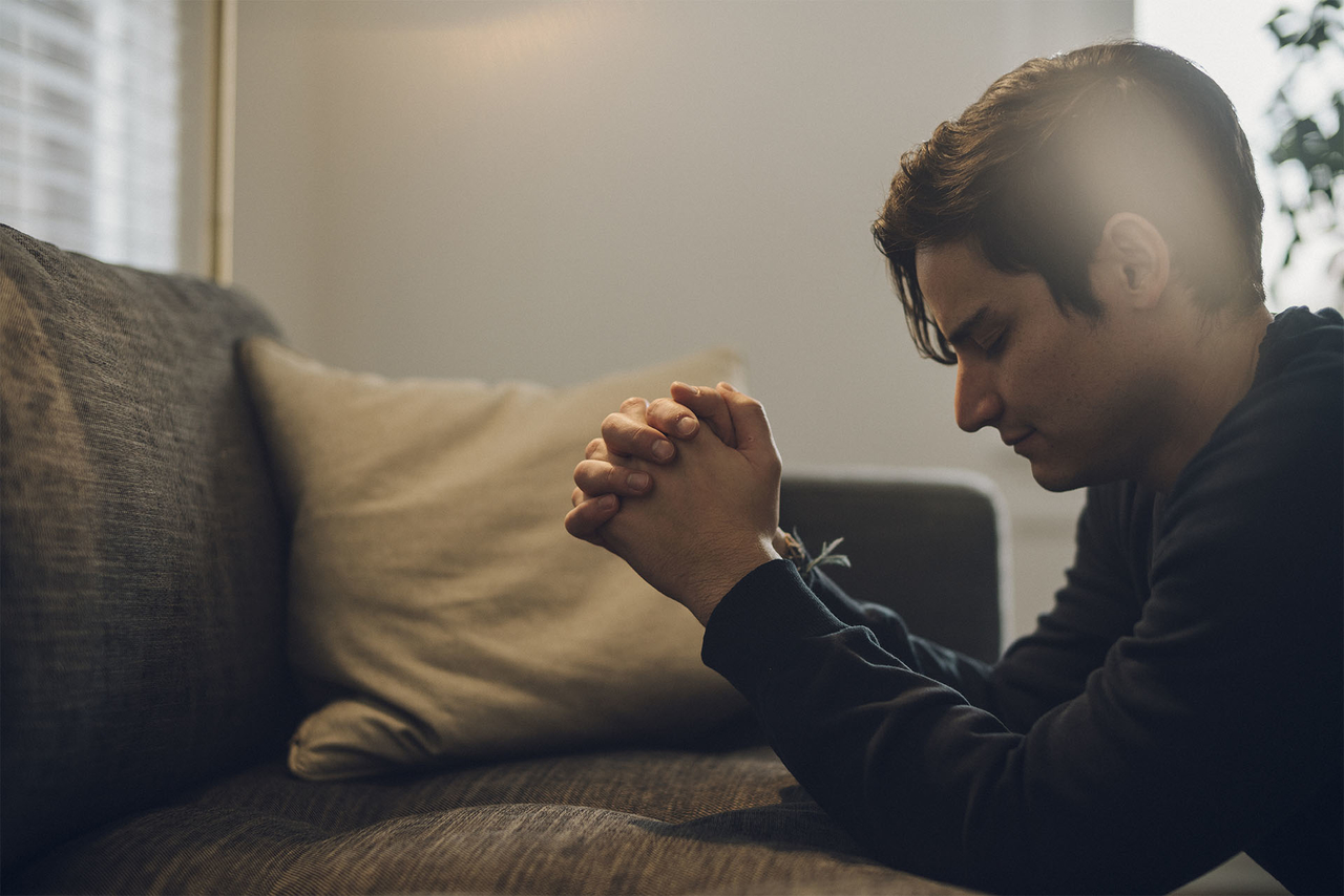 A man kneels in prayer in his living room praying for strength