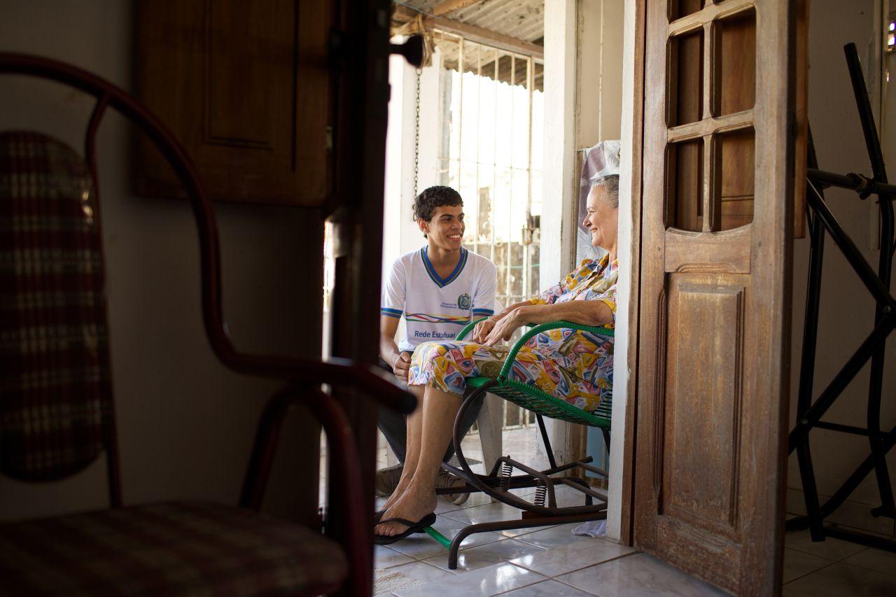 Joven hablando con una mujer mayor en silla de ruedas