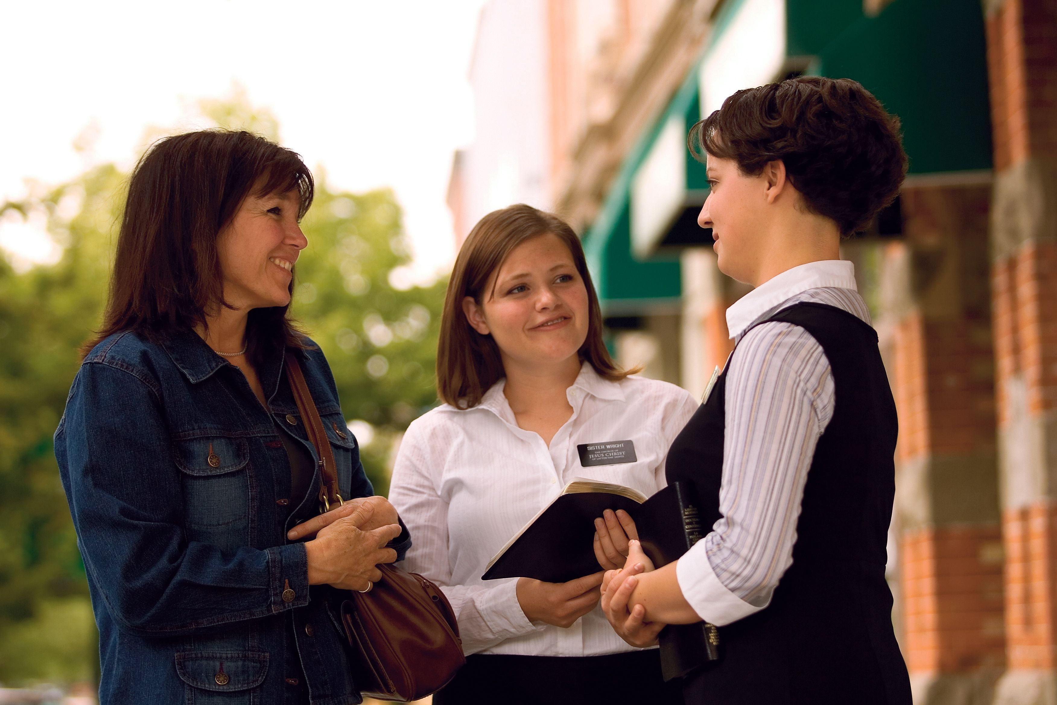Two sister missionaries holding their scriptures and speaking with a woman wearing a denim jacket in an outdoor setting.