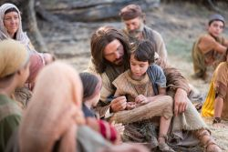 Jesus surrounded by children with one on his lap