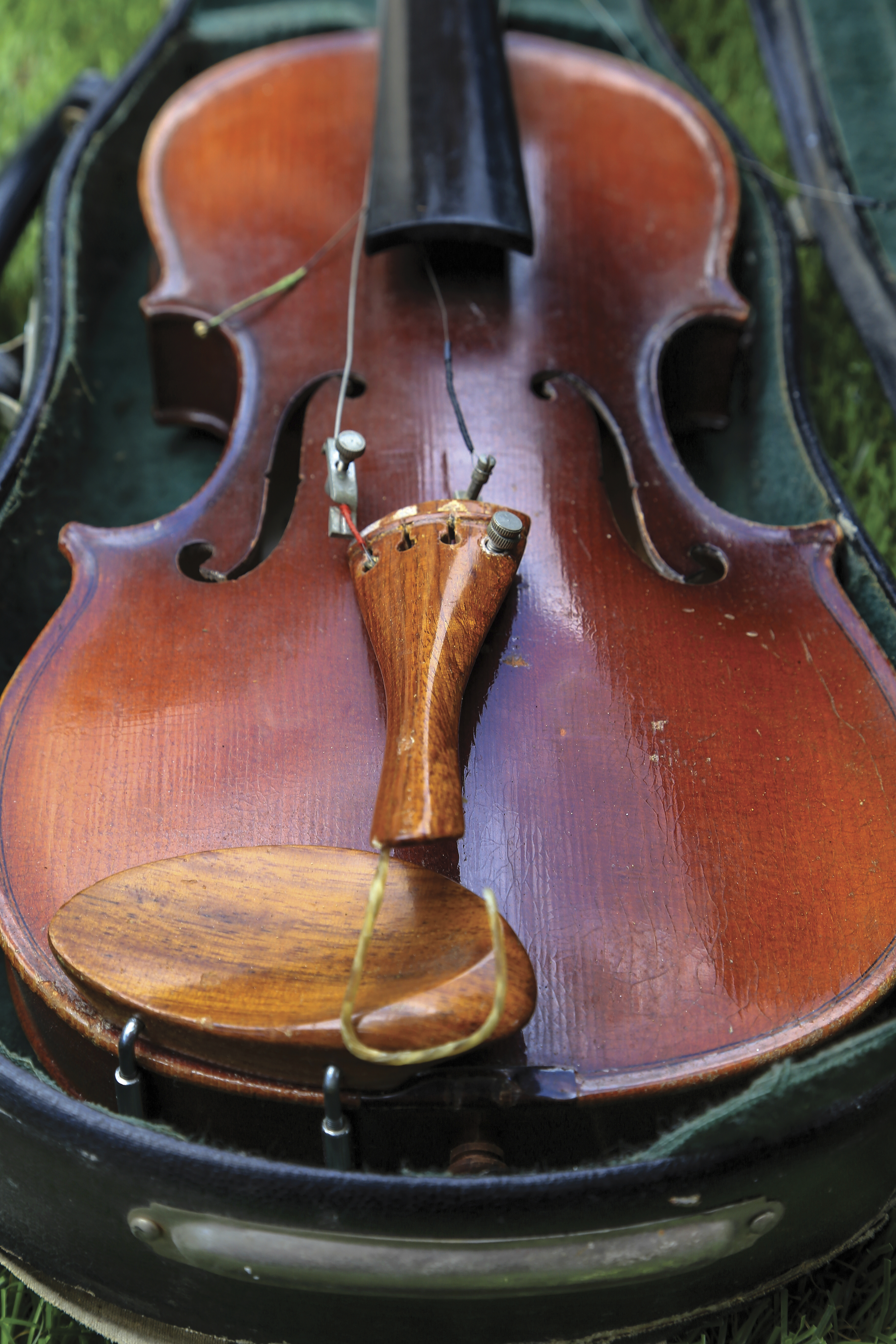 A violin with broken strings lying in a case.