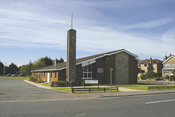 The outside of a dark brown chapel in Ireland surrounded by green grass and a fence in front with a parking lot on the side.