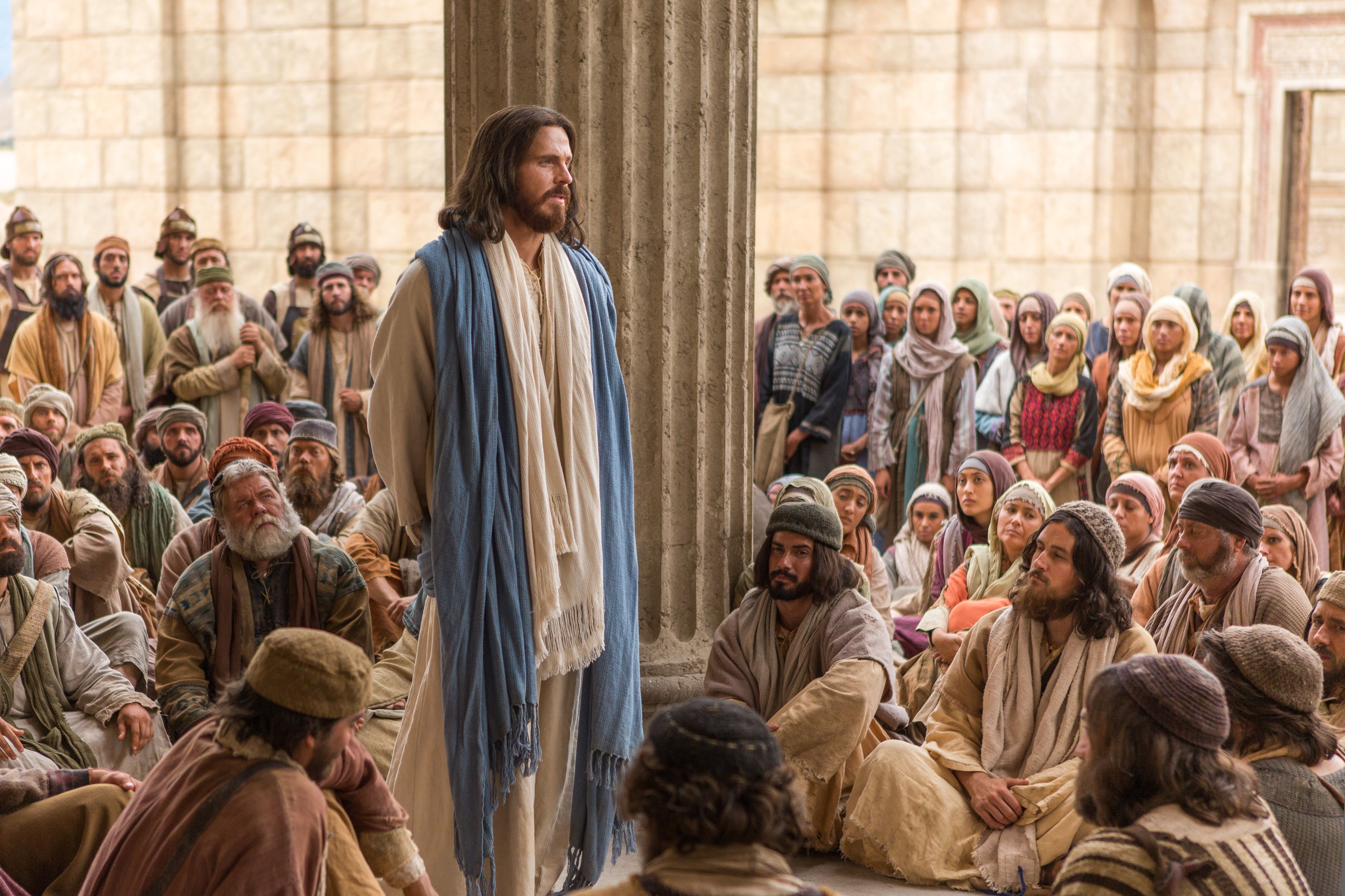 Jesus stands and teaches to listeners around Him.