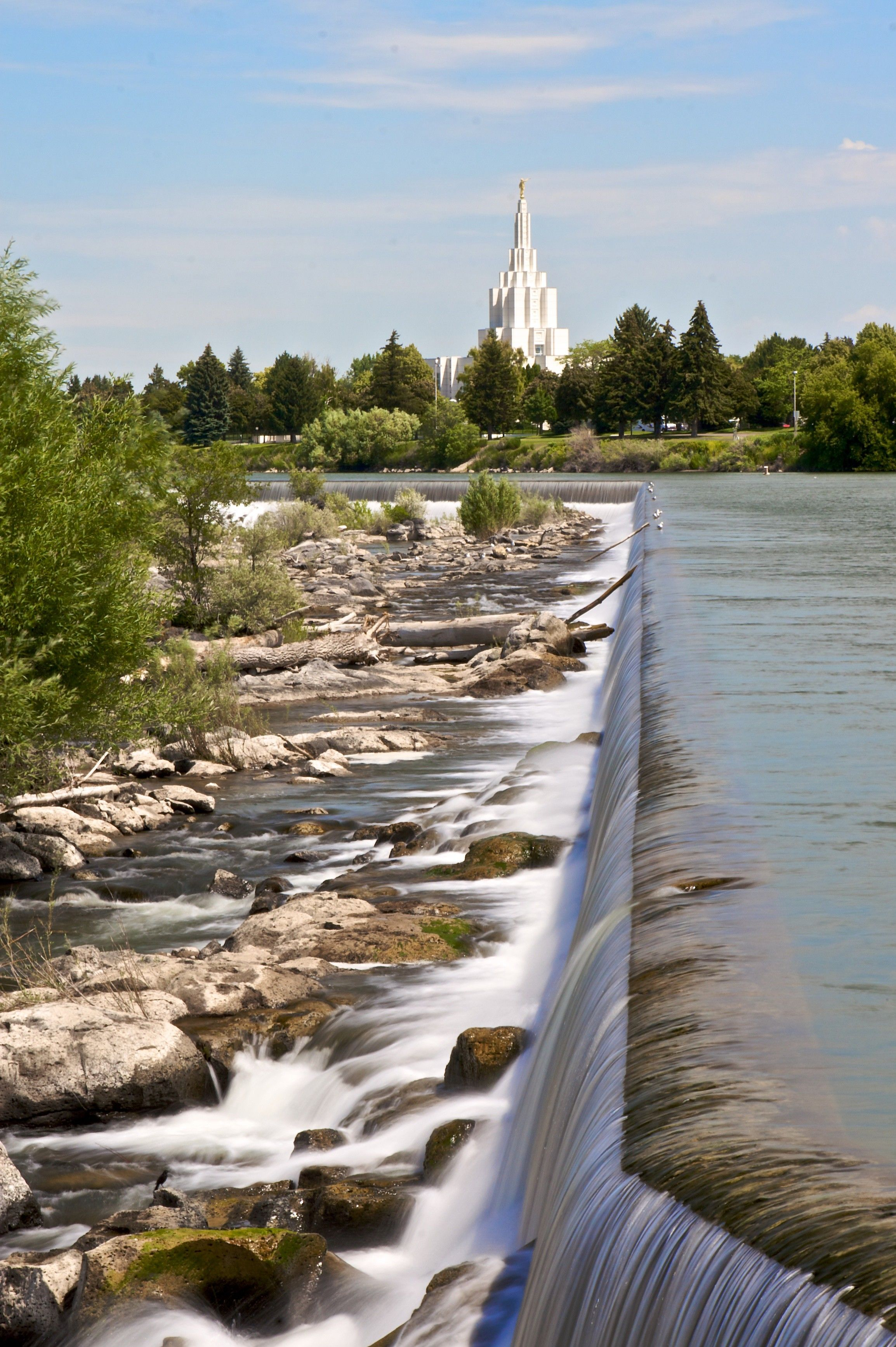 A distant view of the Idaho Falls Idaho Temple, near the waterfalls.