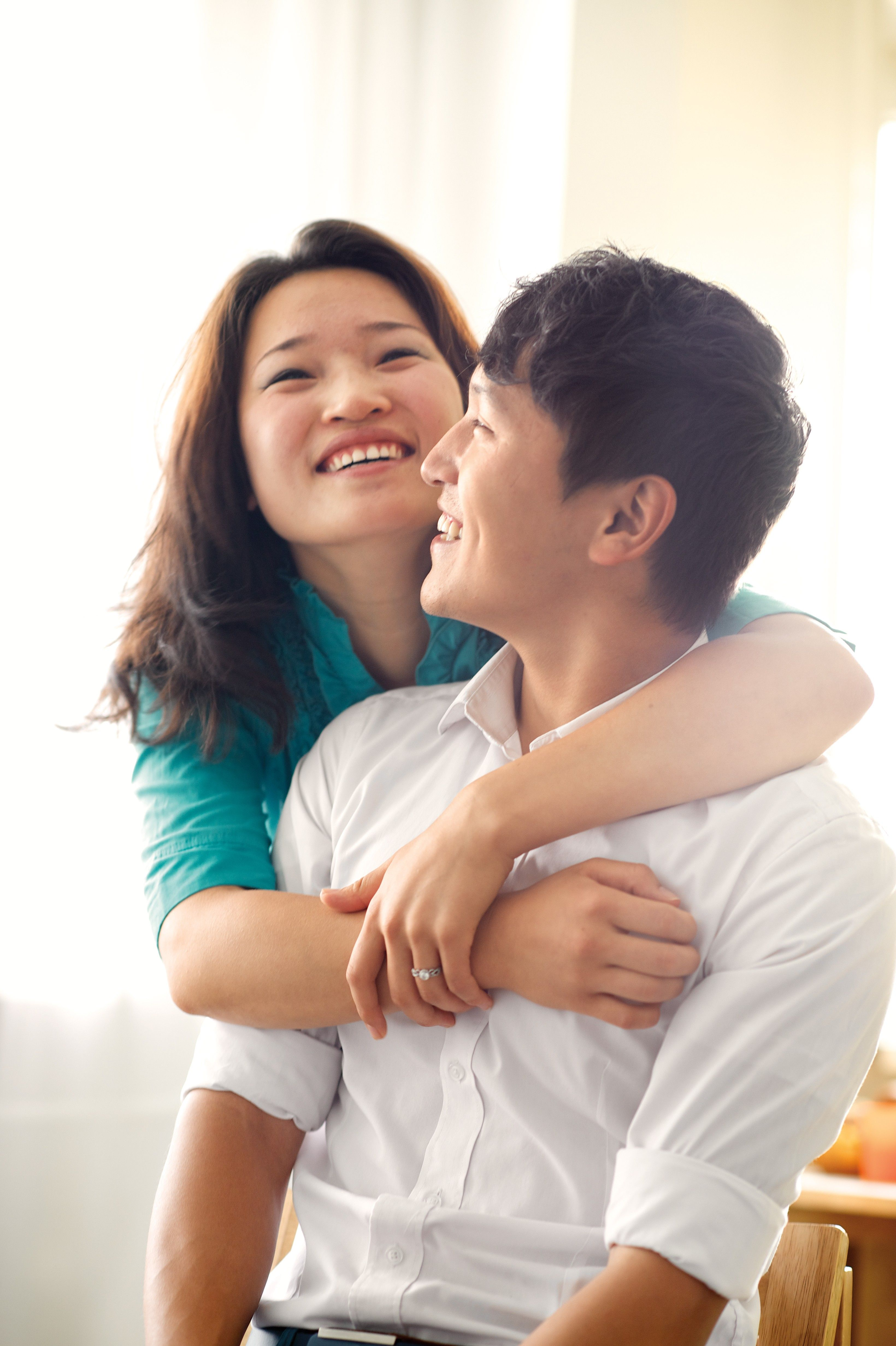 A portrait of a young couple hugging and smiling.