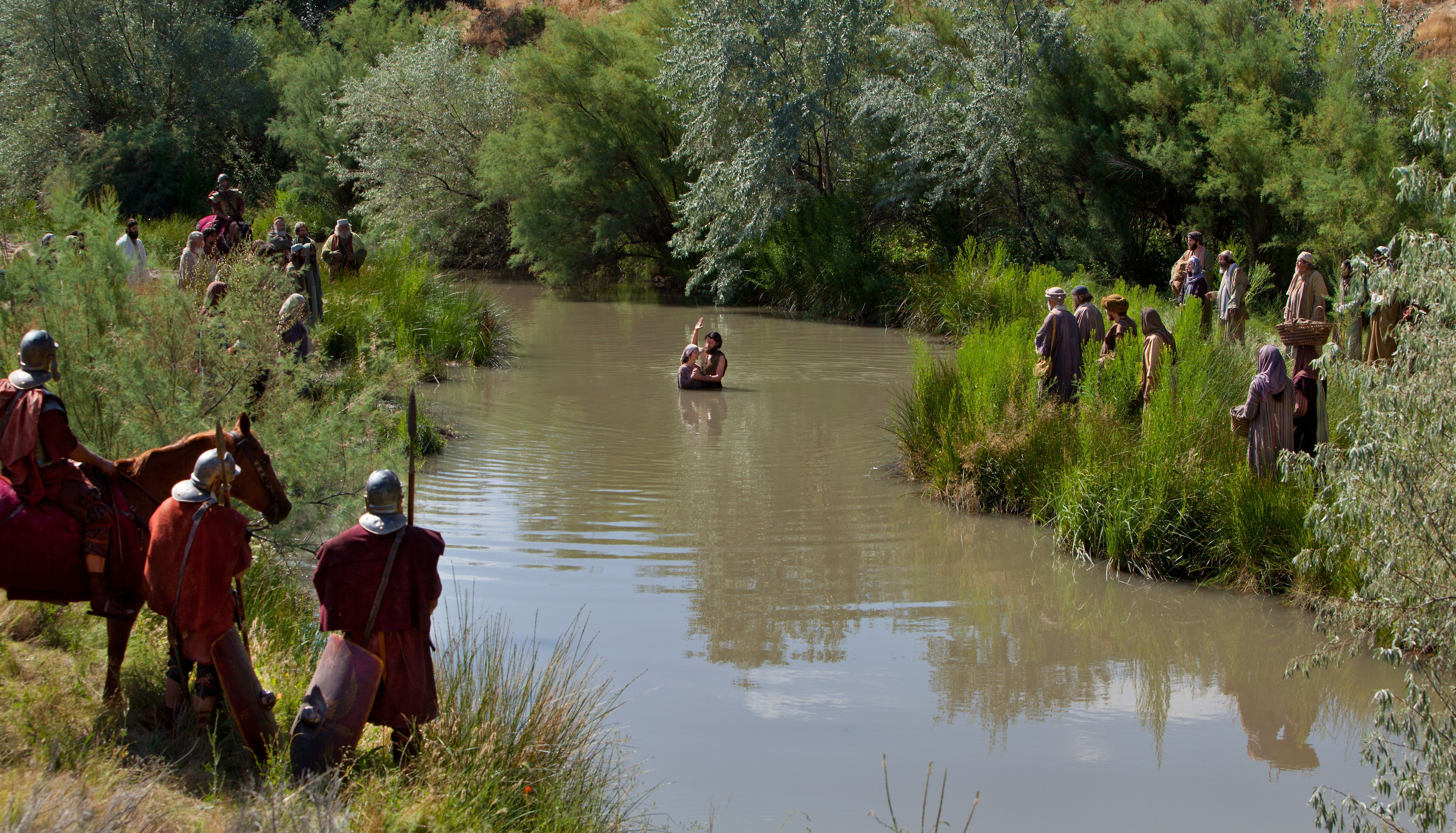 John baptizes men and women in the River Jordan.