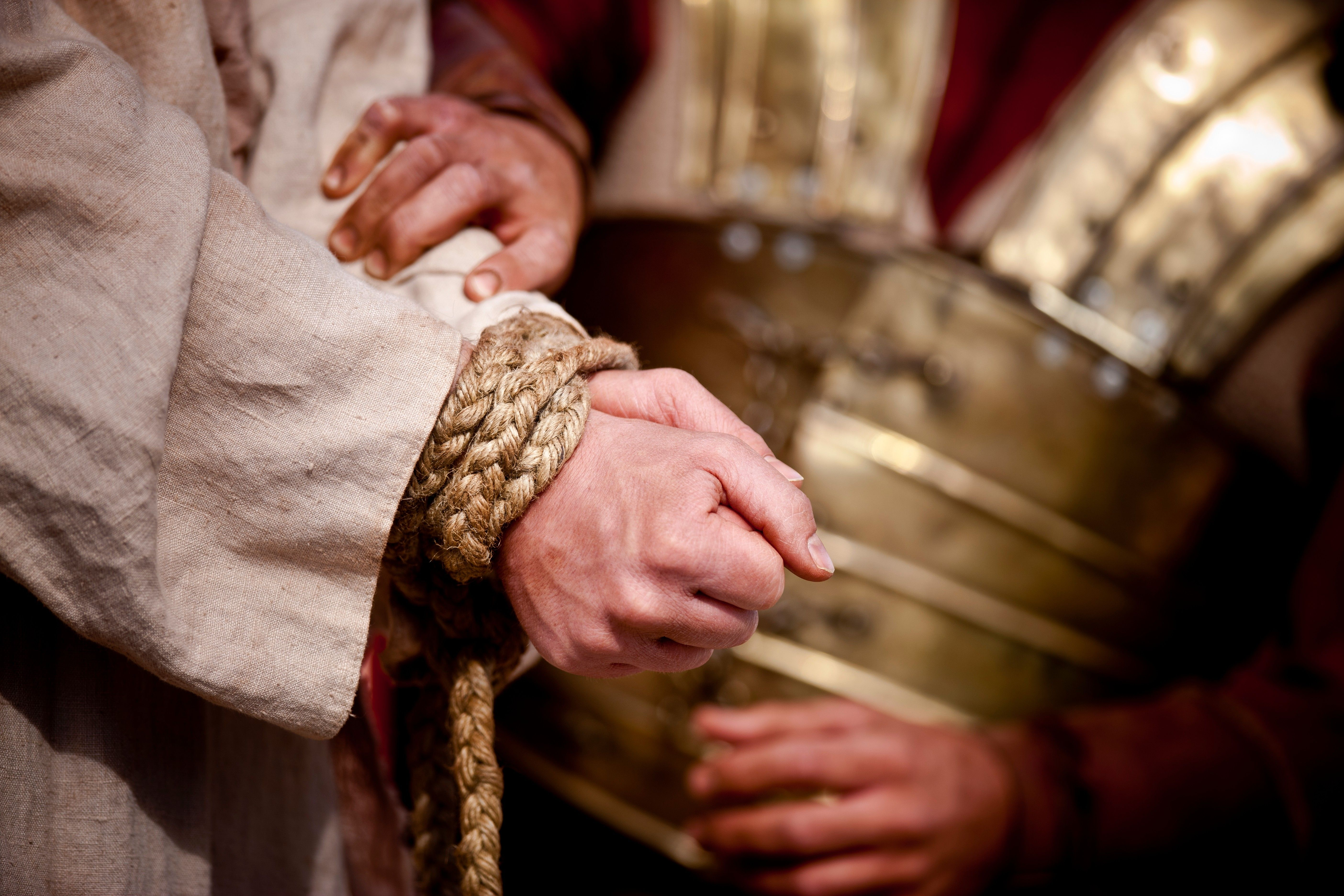 A Roman soldier binds the hands of Christ together.