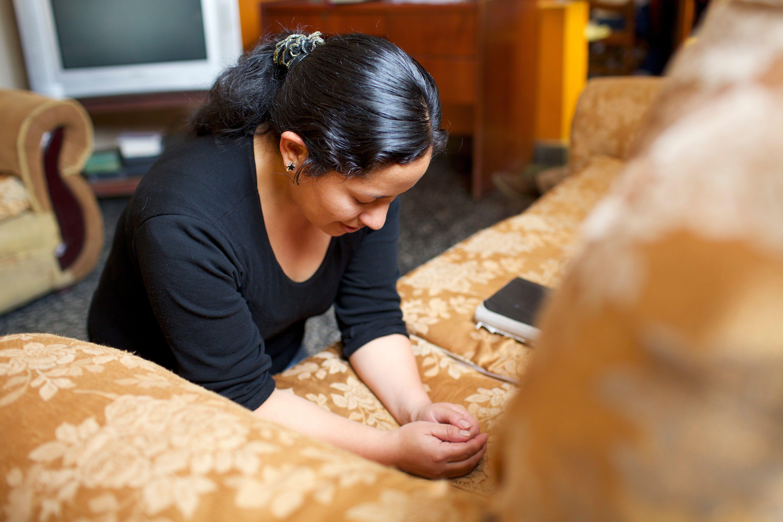 A woman kneeling in prayer.