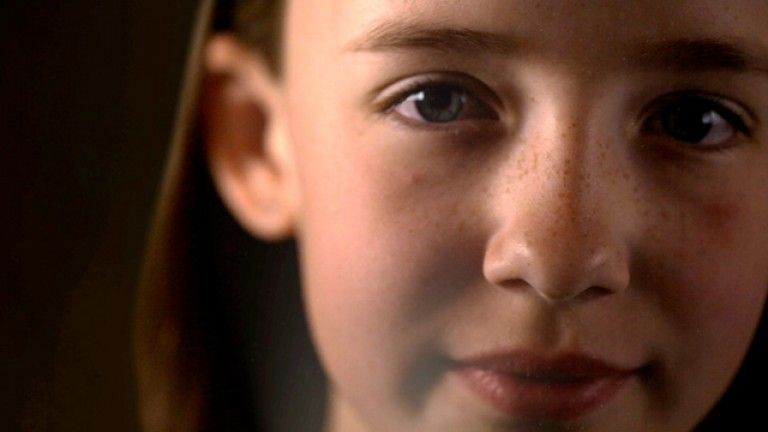 A photo of a young girls face, up close while looking at the camera.