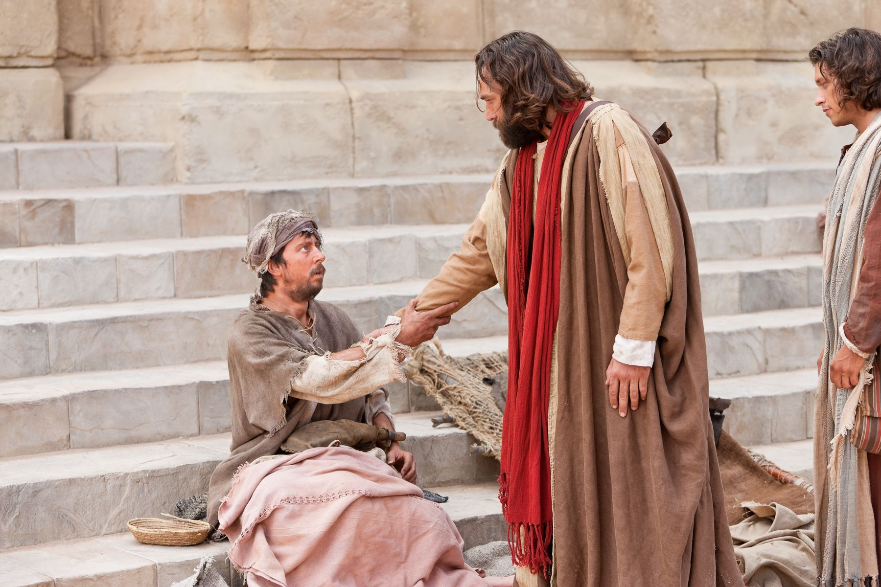 Peter reaches out his hand to a crippled man and commands him to rise and walk.