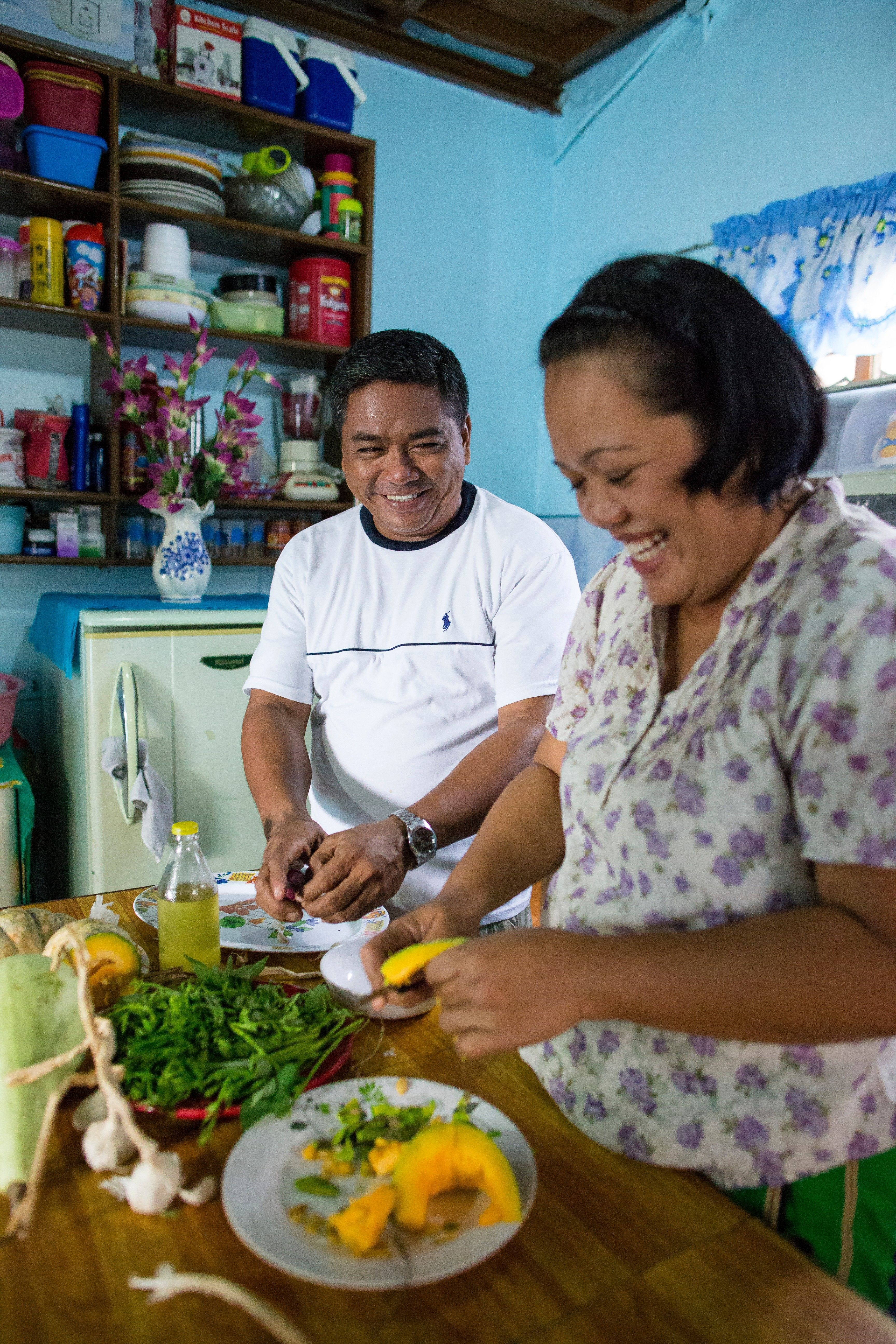 A couple from the Philippines standing in a kitchen and preparing food together.