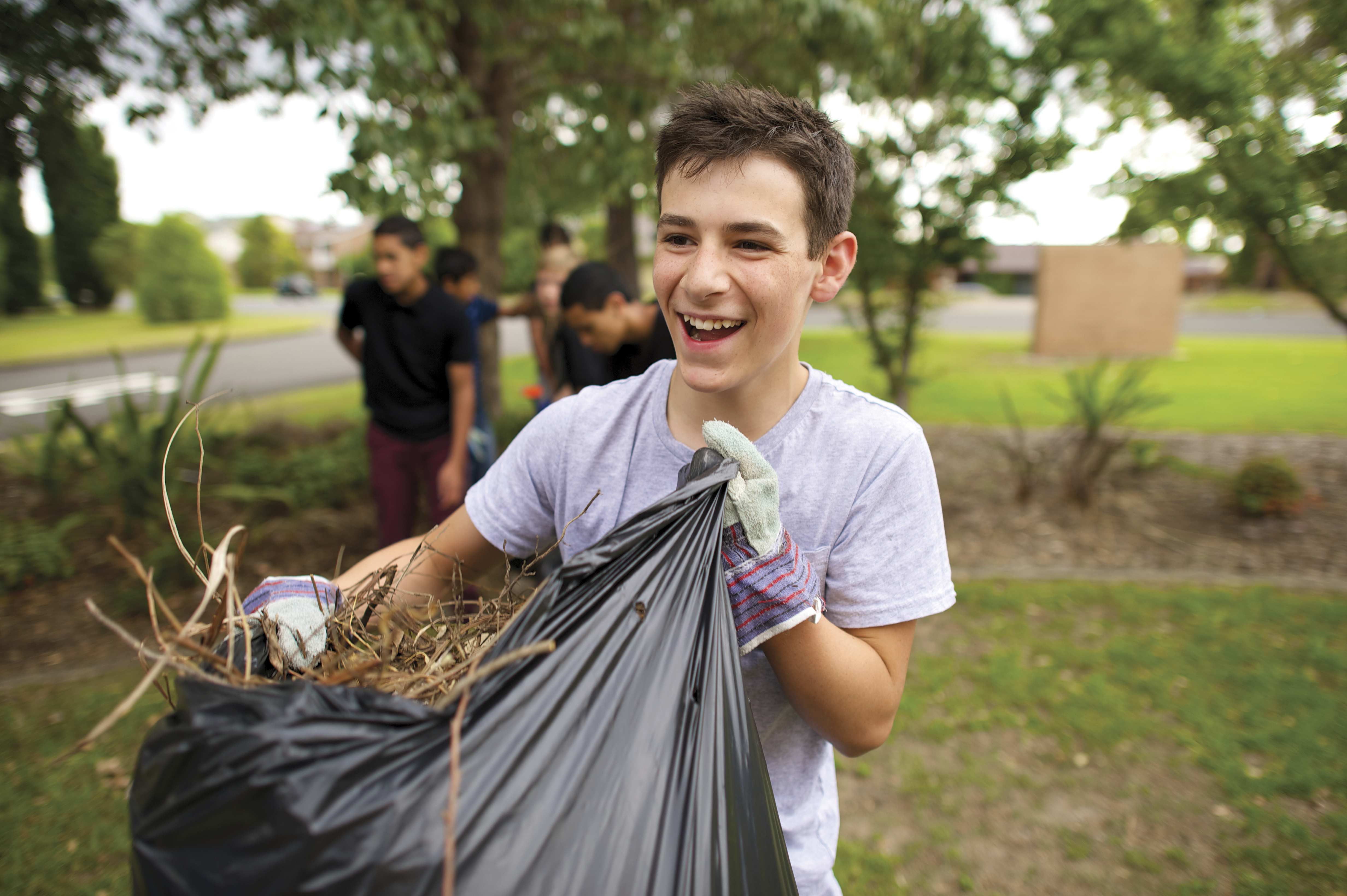 A group of young men clean up a yard.
