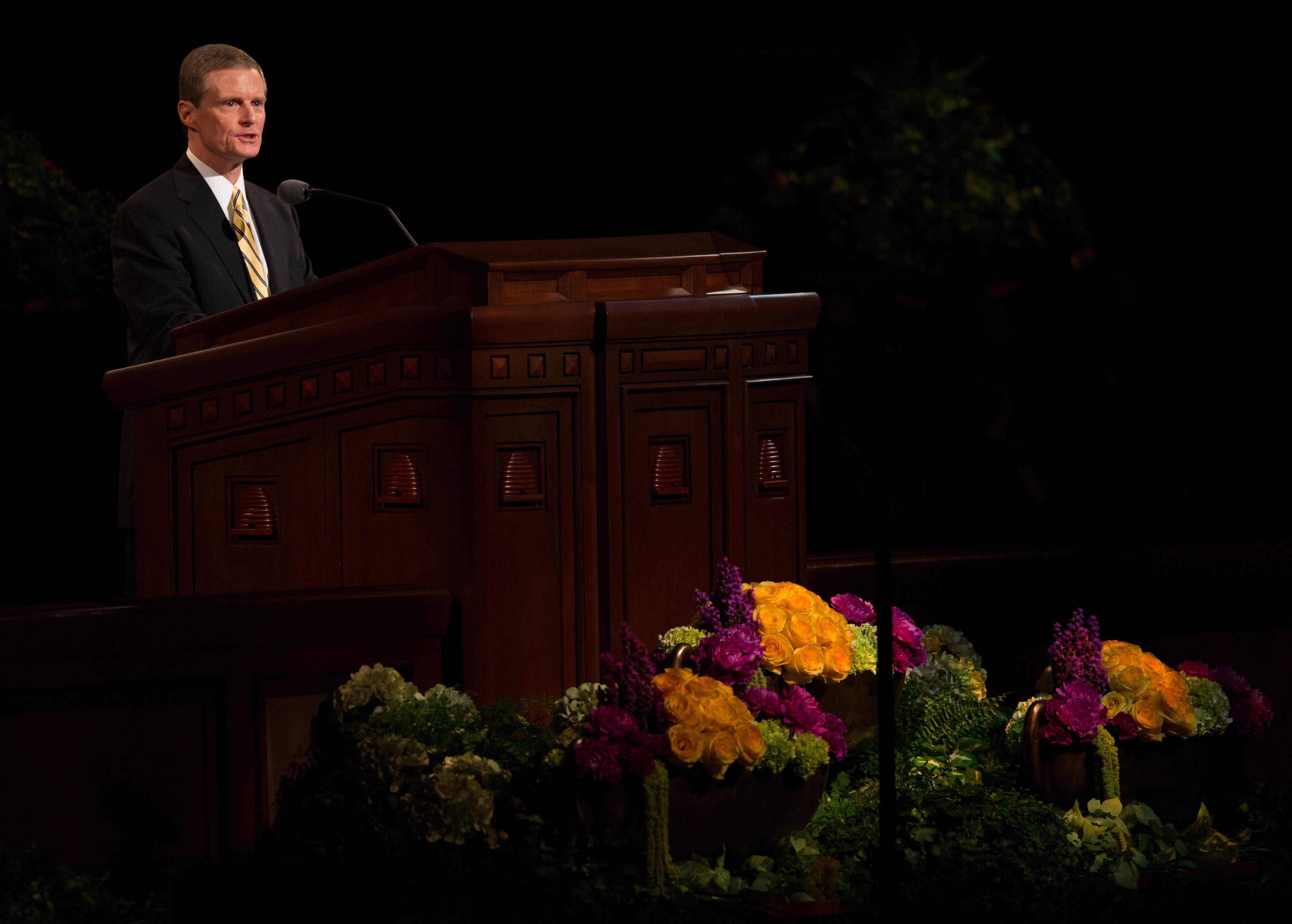 David A. Bednar standing at the pulpit and speaking at general conference.
