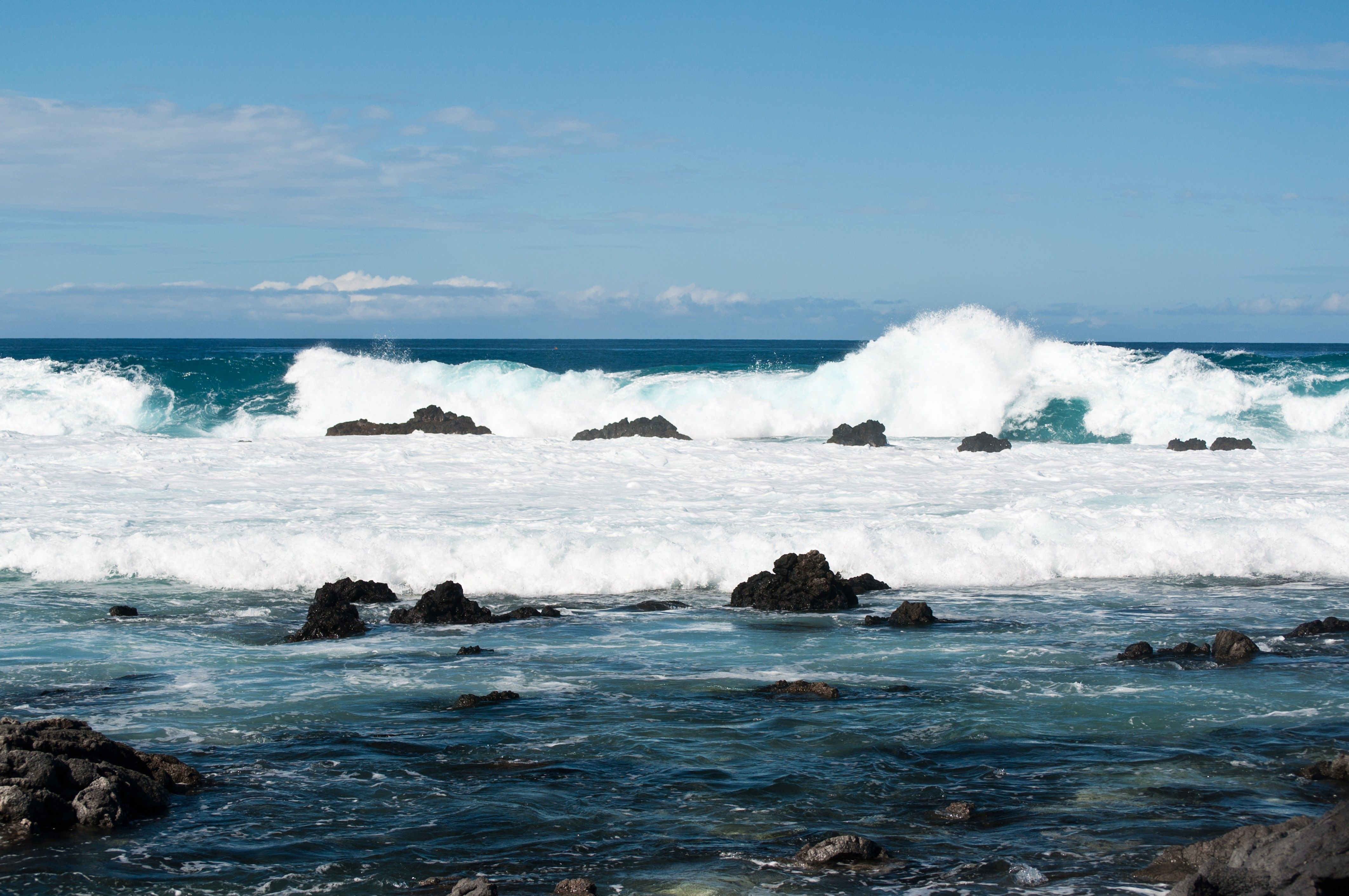Rocks rise above the waterline in Hawaii.