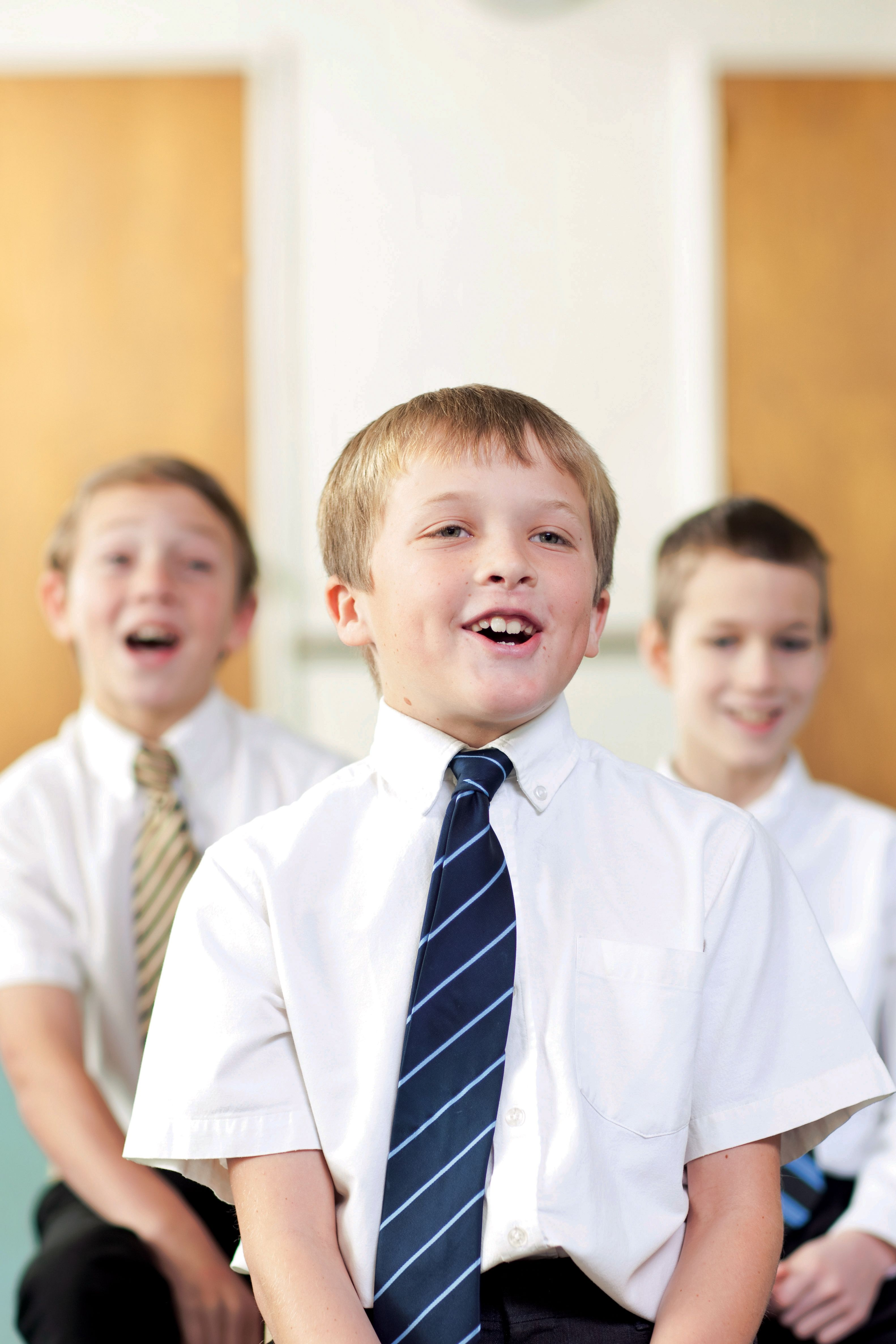 Three Primary-age boys sitting and singing together.