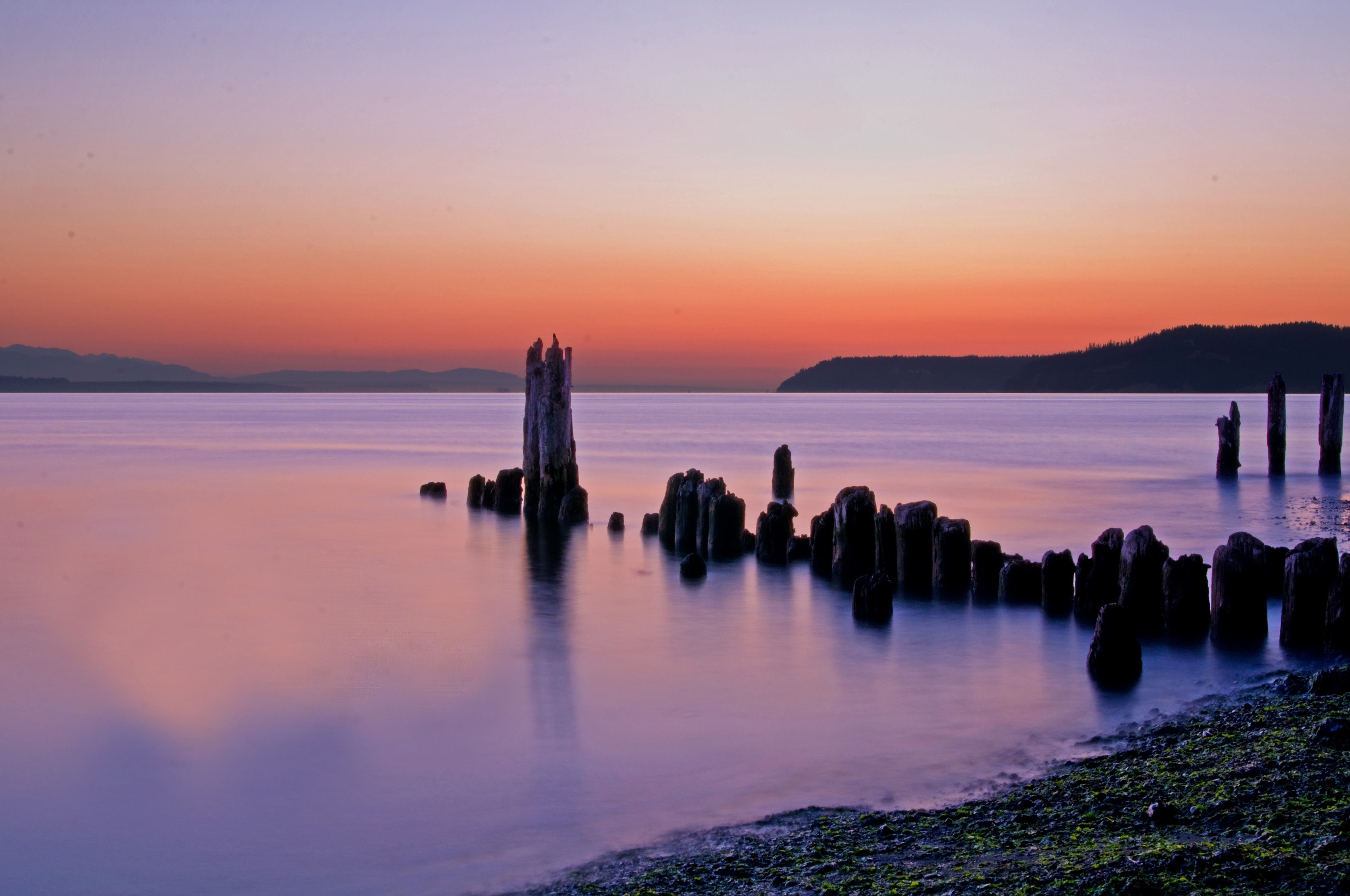 An old pier extends out into the water, with a sunset in the background.